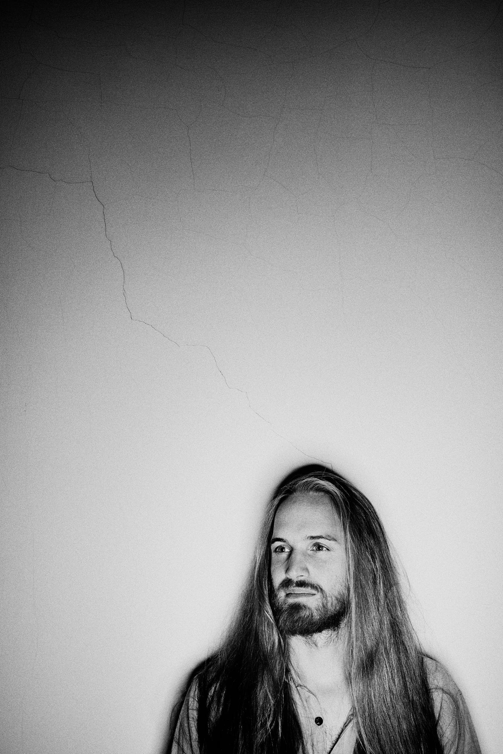 Black and white portrait of a man with long hair with a crack in the wall running across the image behind him.