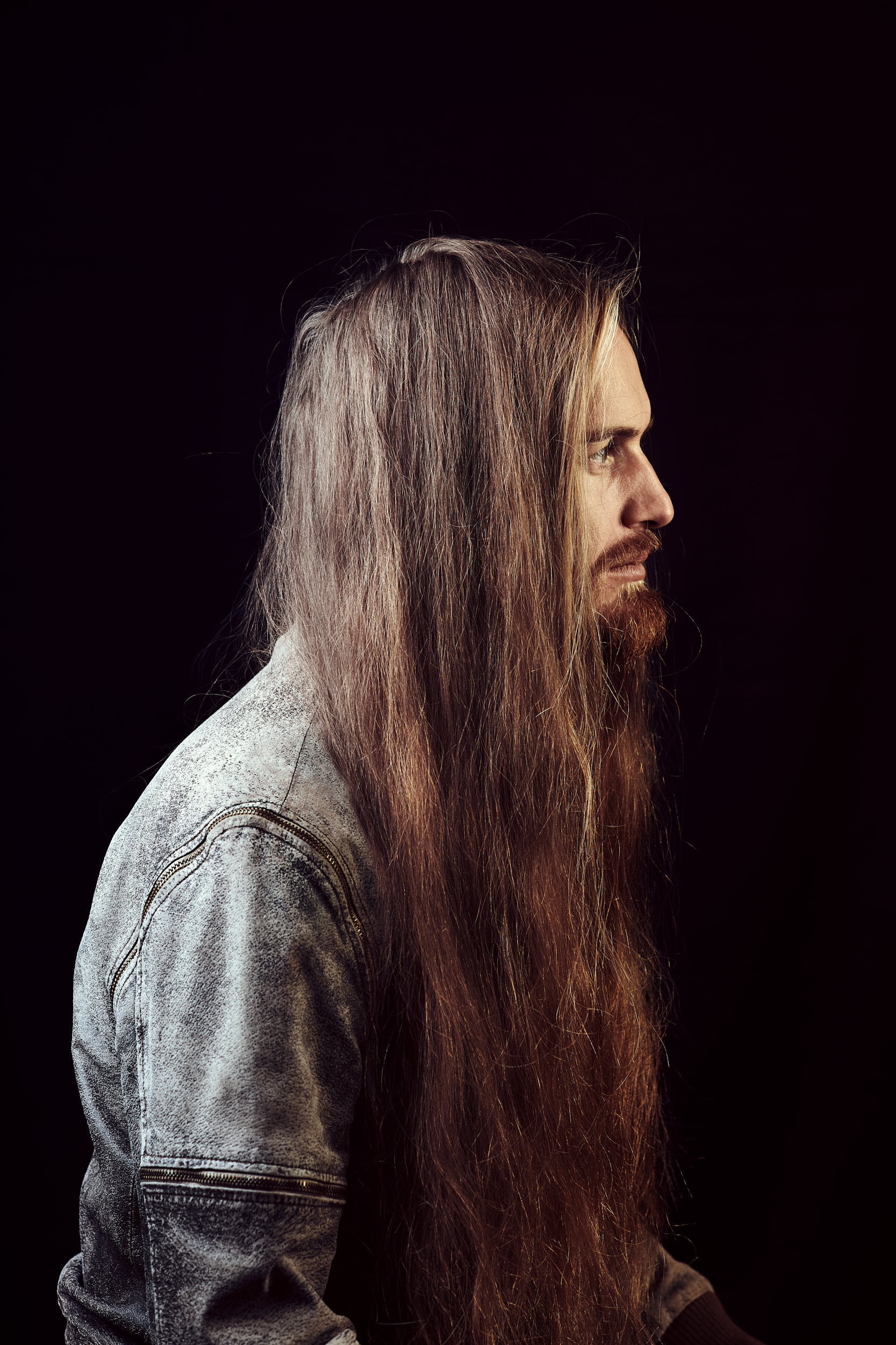 Classic portrait photography: Man with long hair in a studio setting.