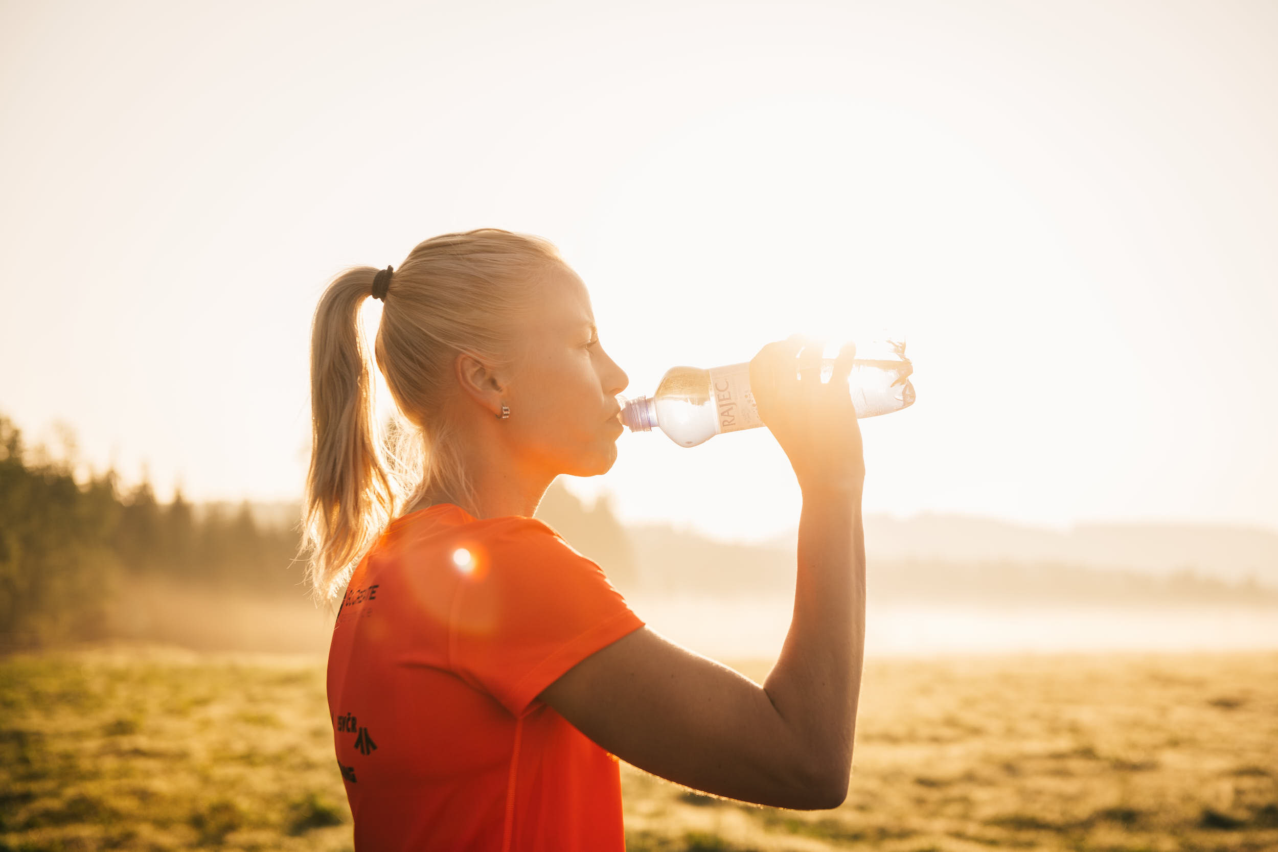 Female runner drinking water in a beautiful sunlit landscape.