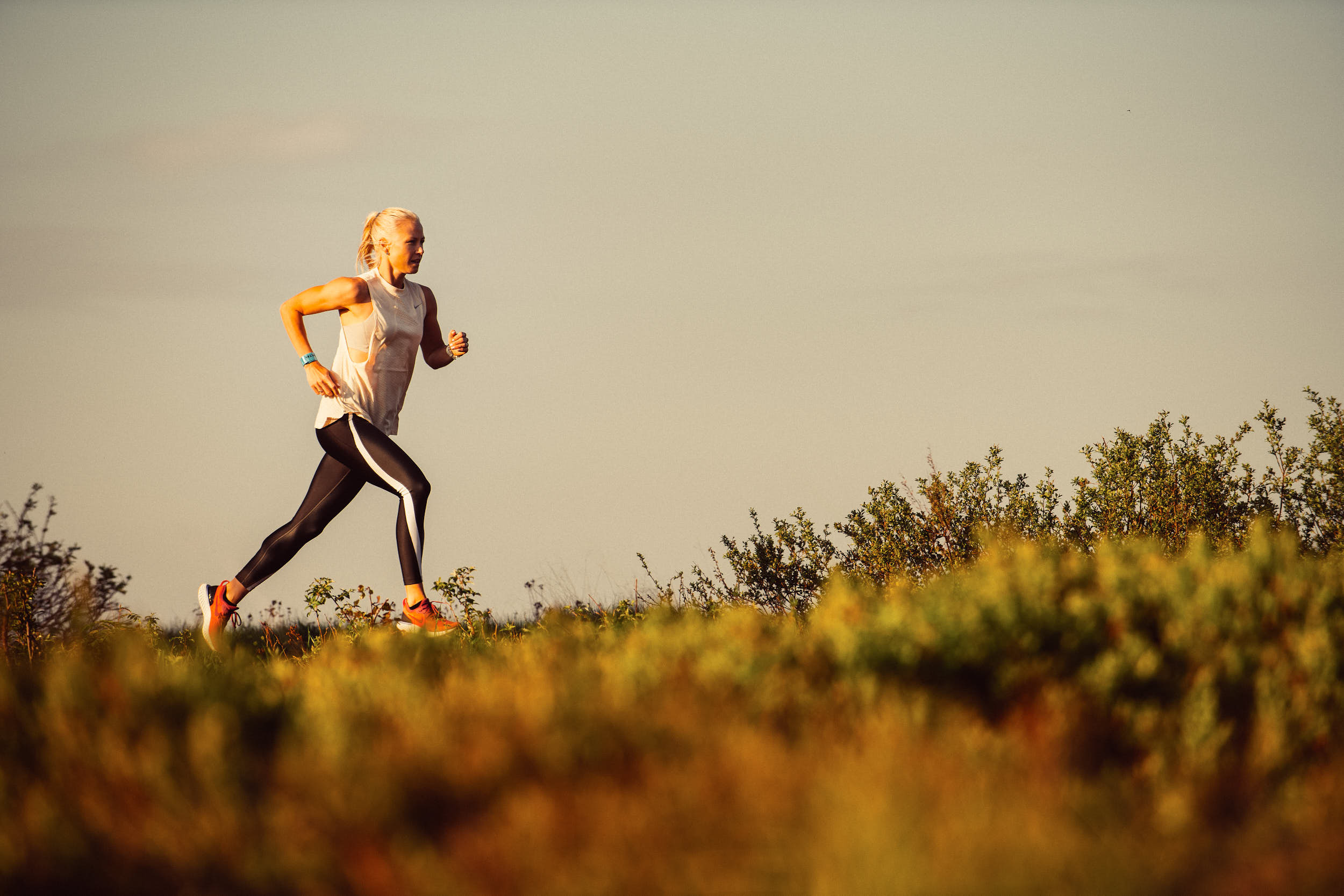 Woman running through a mountain meadow in beautiful morning light.