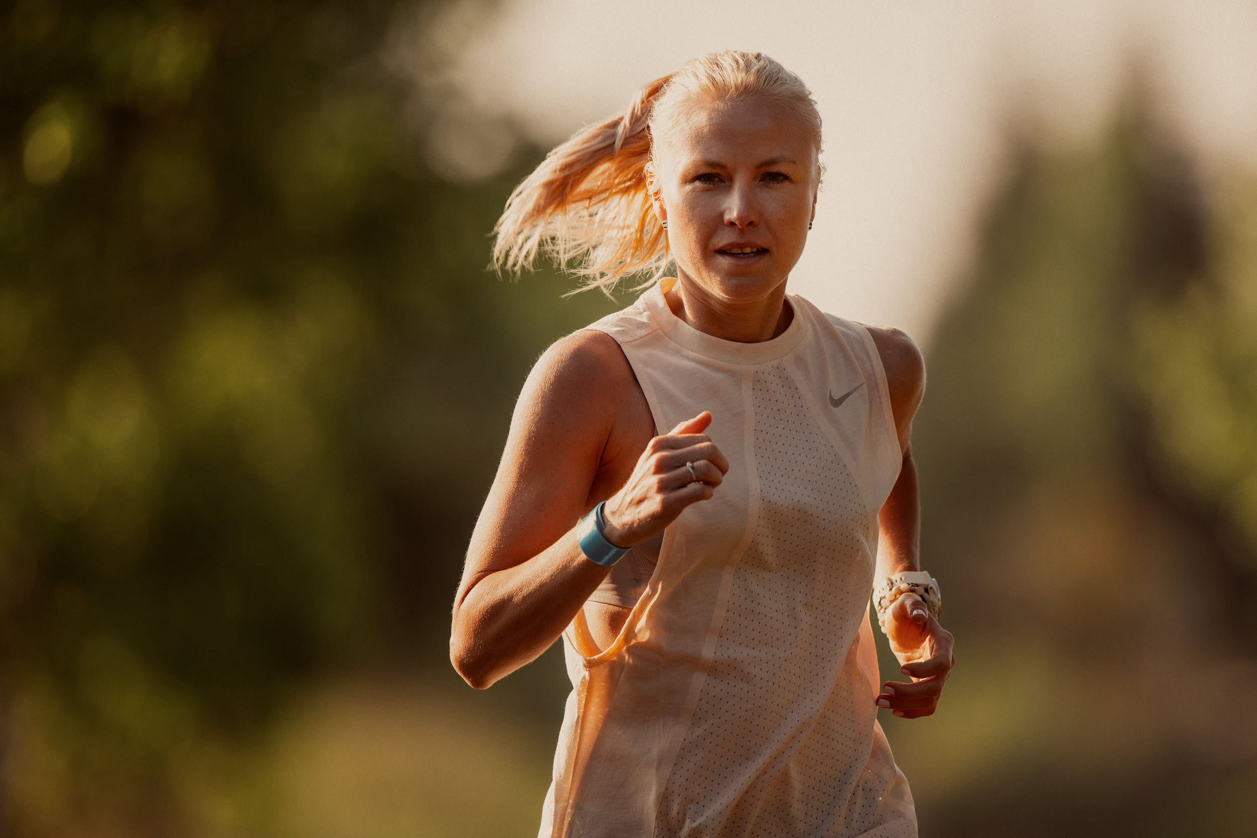 Medium close-up of a female runner in tank top with blurred trees in the background.