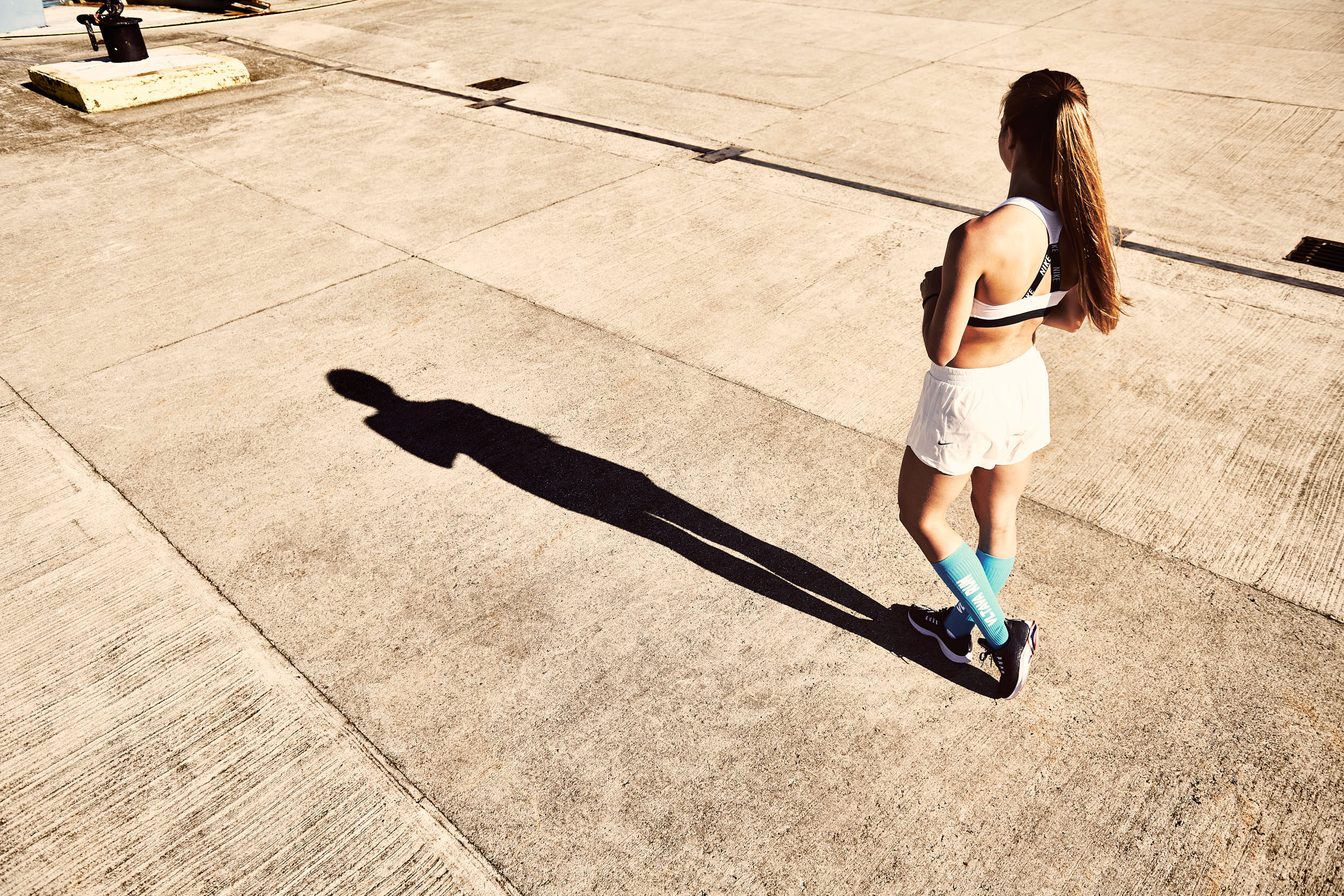 Girl posing in running apparel. Photograph with strong contrast and long shadows.
