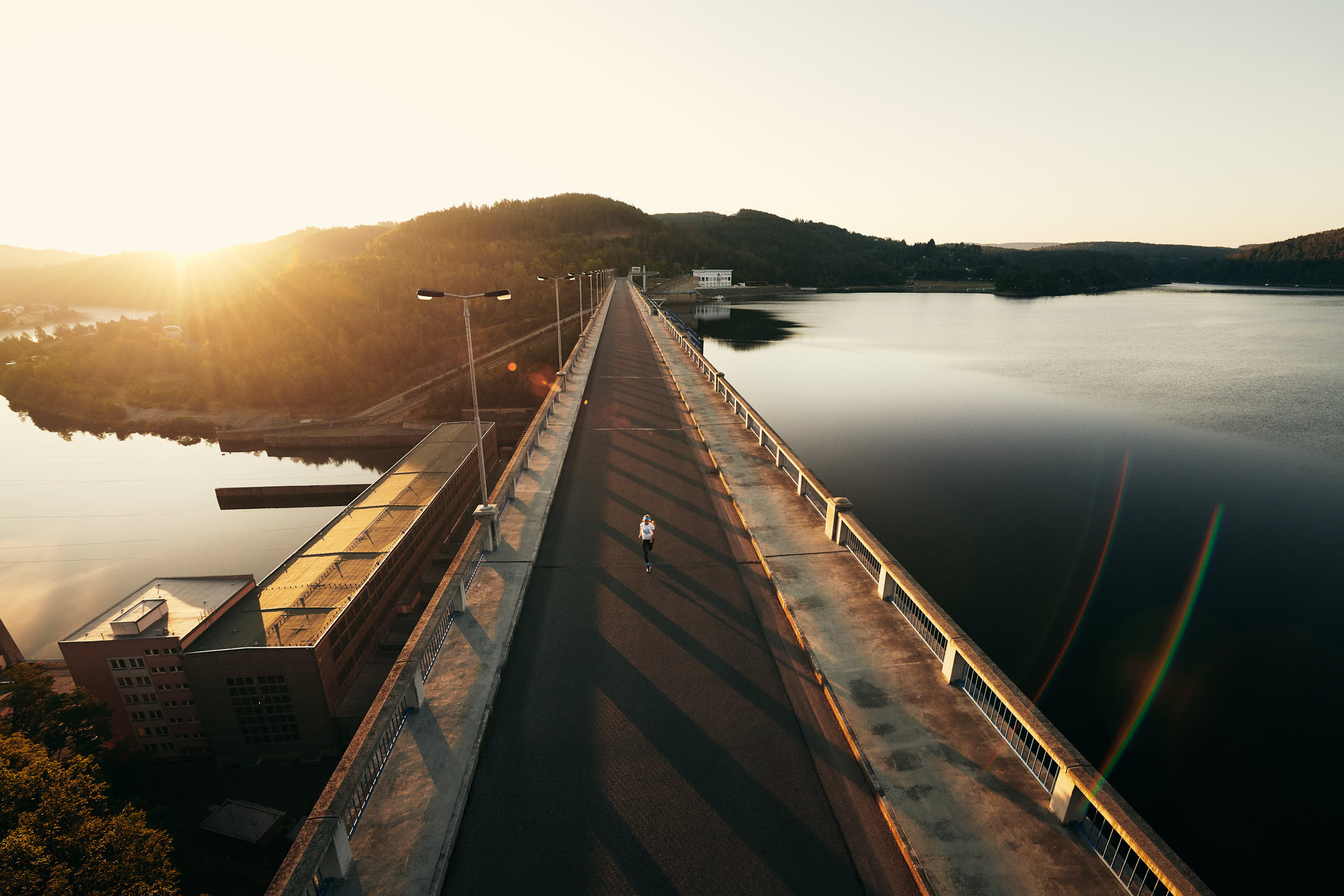 Sport advertising photography: girl running across a bridge in beautiful morning light.
