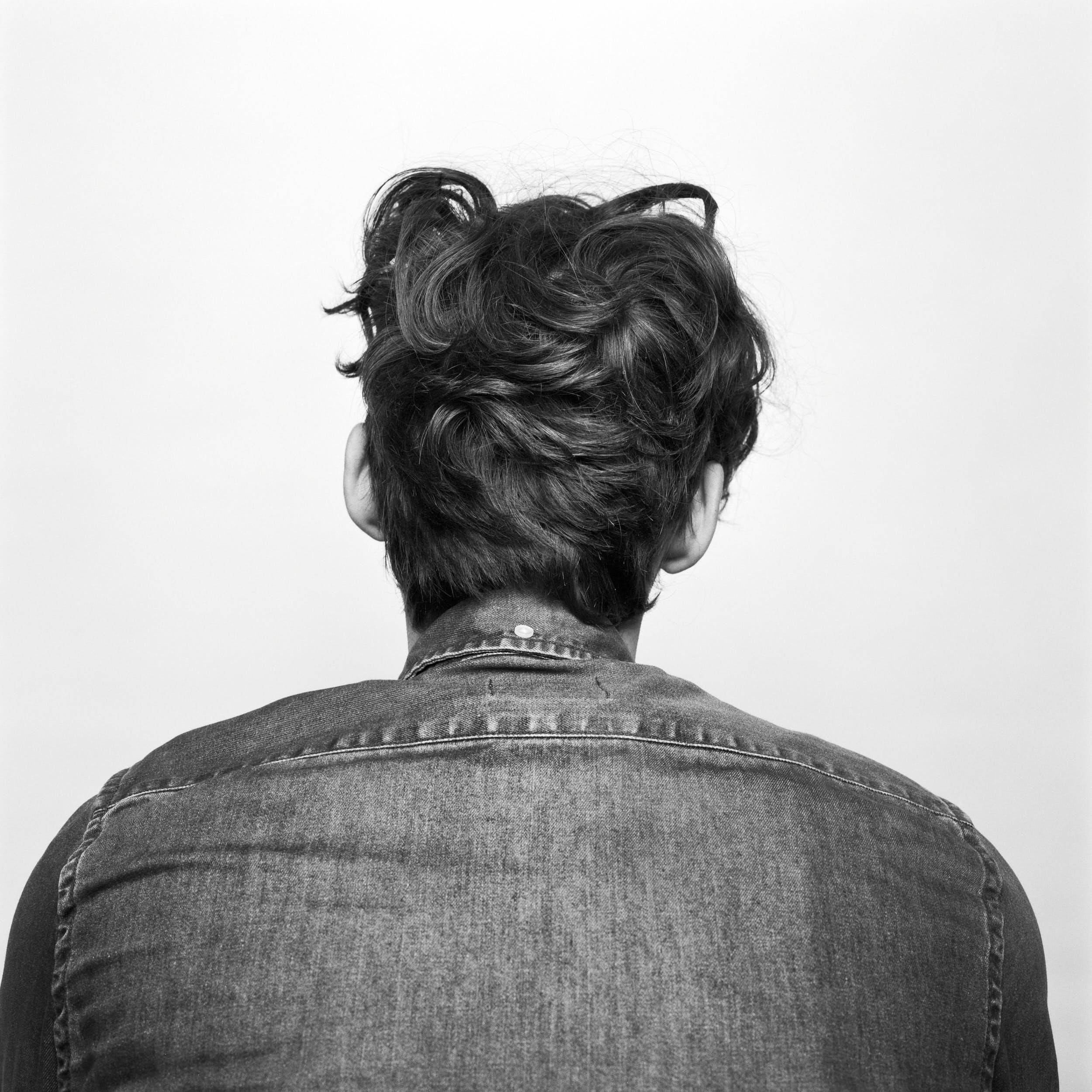 Studio portrait photography: man with curly hair and denim shirt turned away from the camera.