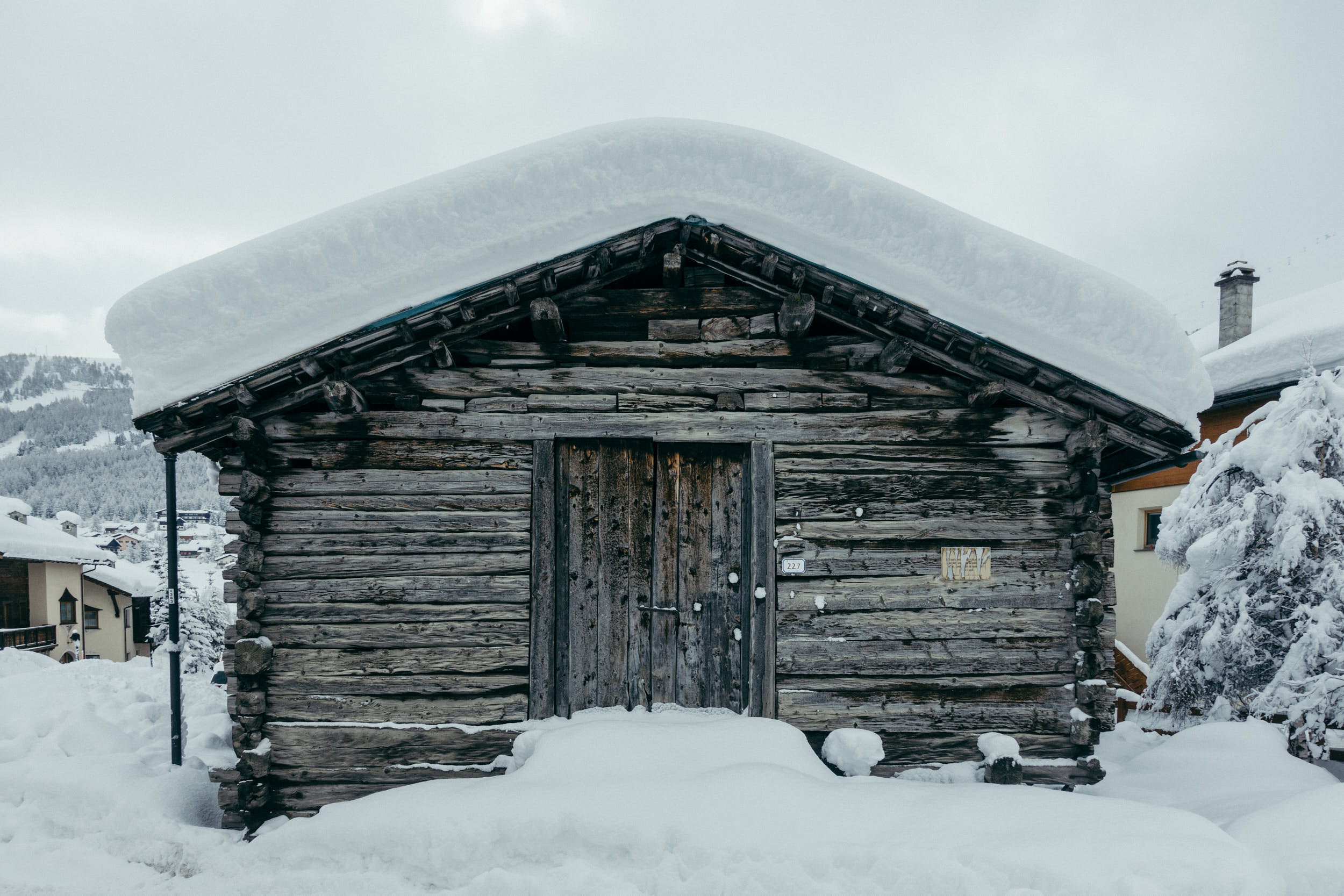 Old mountain hut with a big layer of snow on the roof.