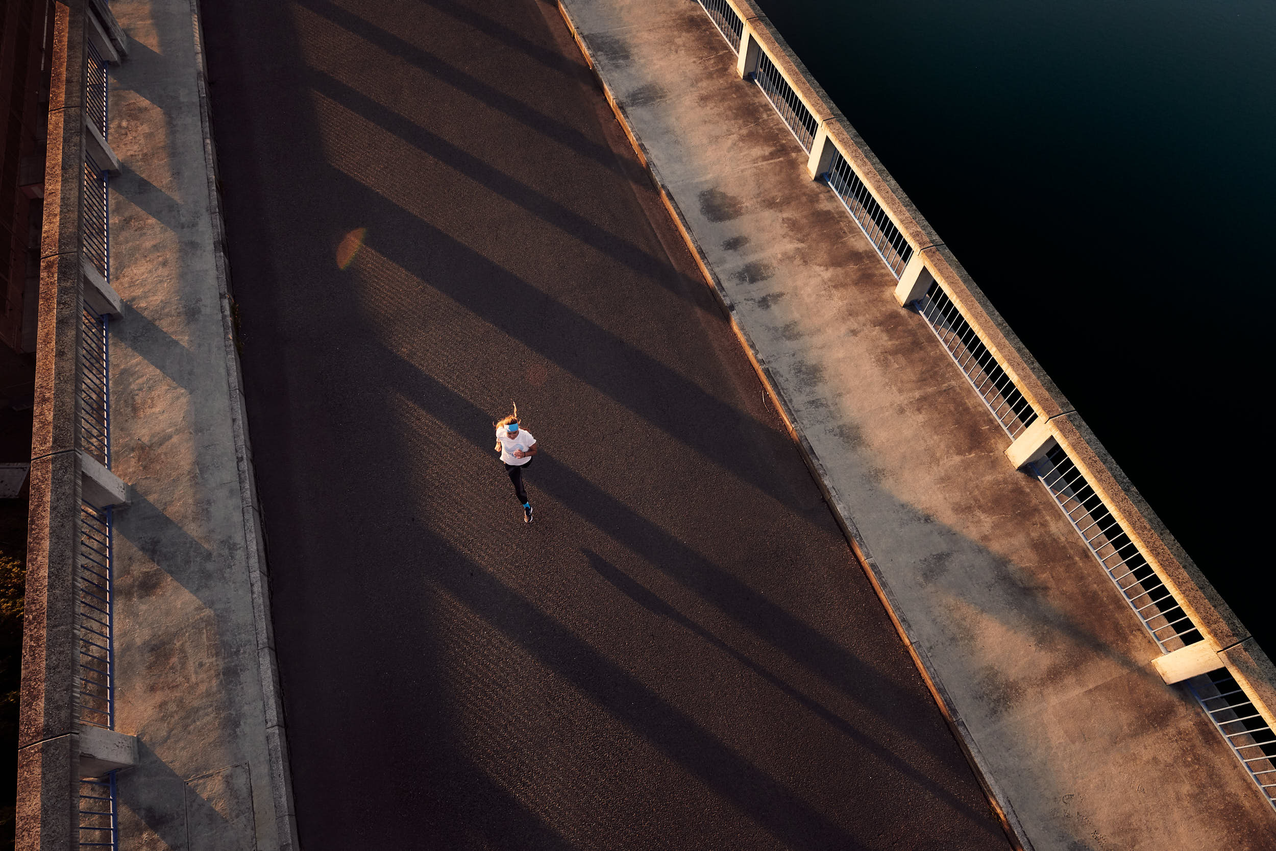 Sport advertising photography: girl running across a bridge in beautiful morning light.