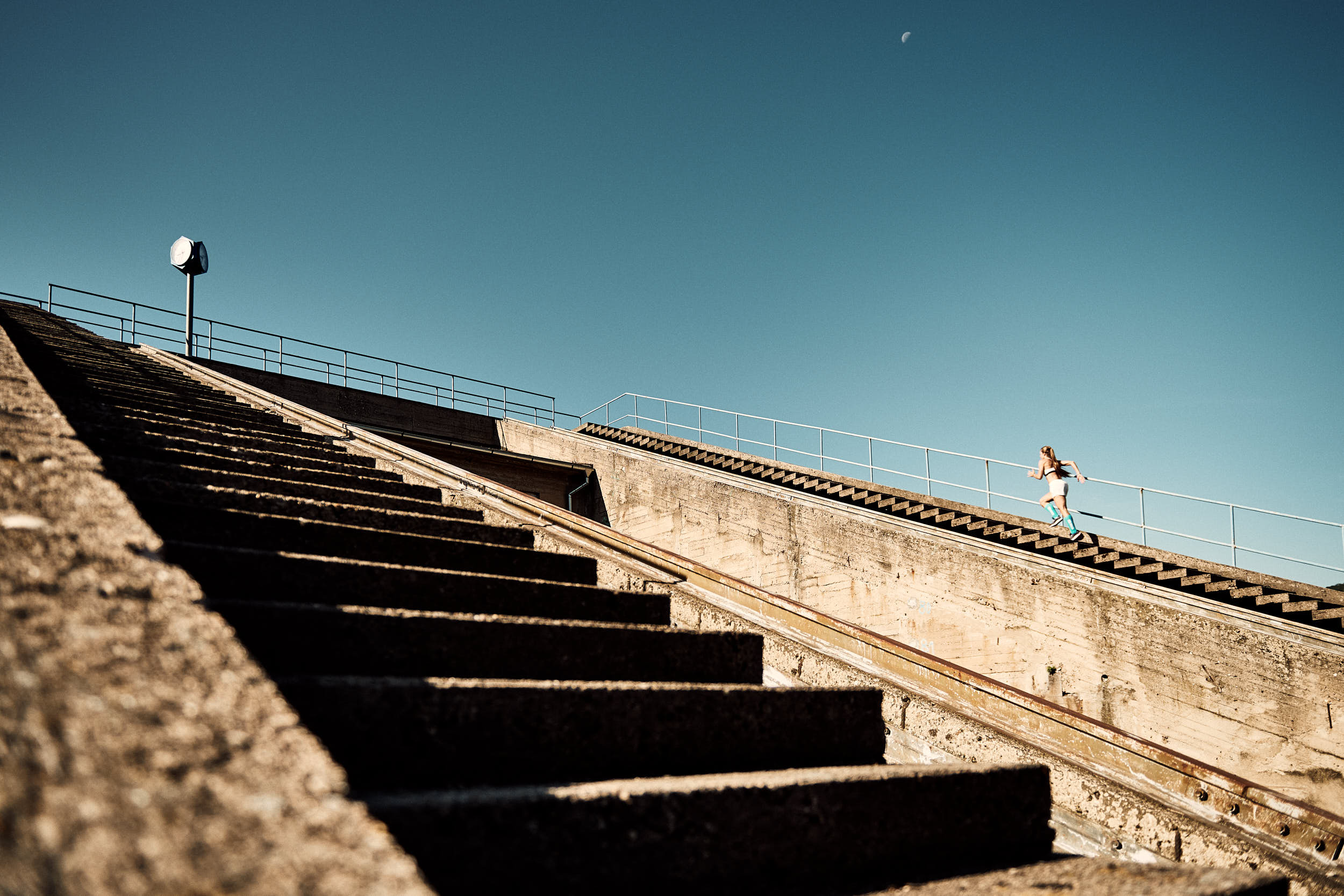 Action photography of a girl running up the stairs of a concrete structure.