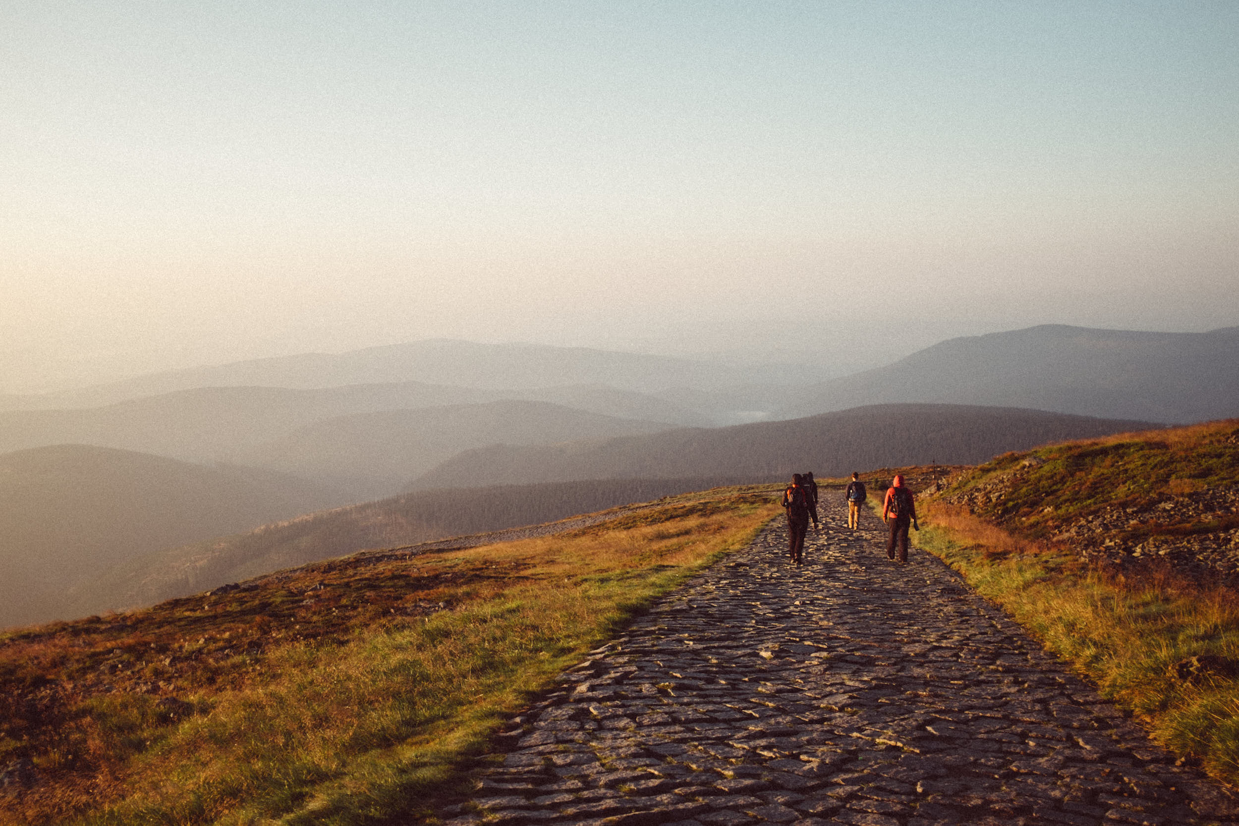Beautiful landscape photography with a group of people descending a mountain at dawn.