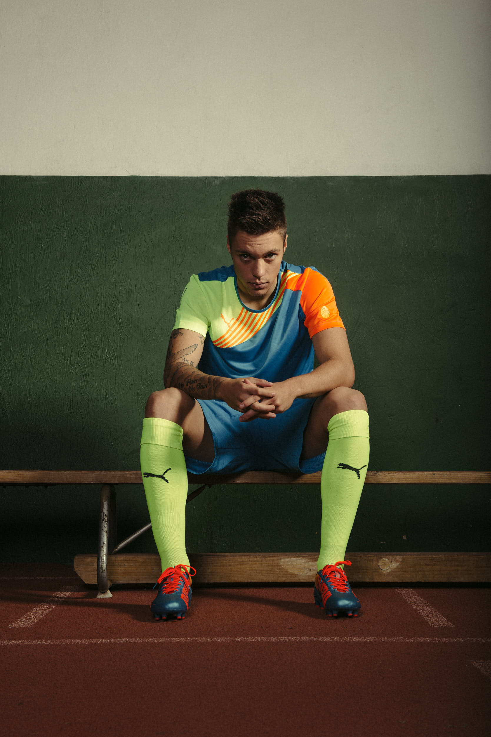 Brand campaign imagery: Professional football player Václav Kadlec sitting on a bench in football apparel.