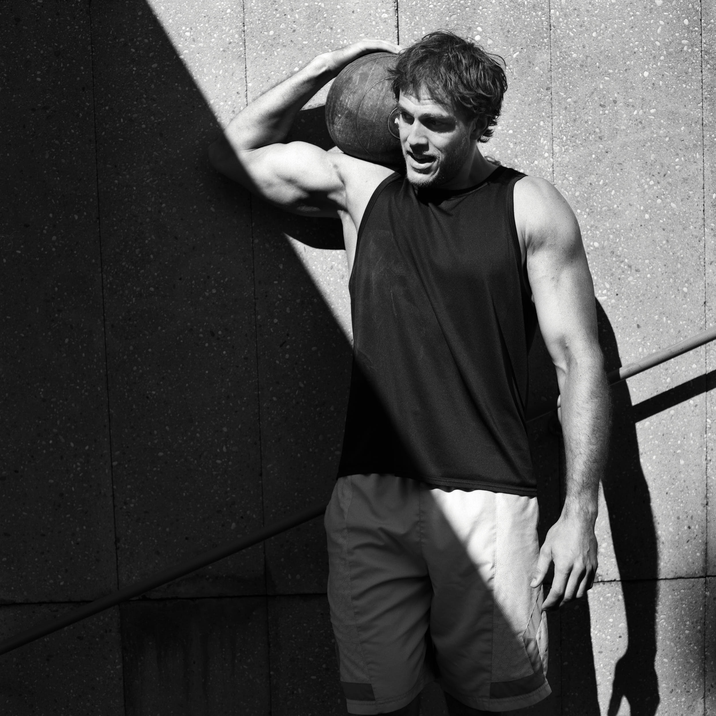 High contrast active lifestyle photography: strong fitness athlete holding a medicine ball in a black and white portrait.