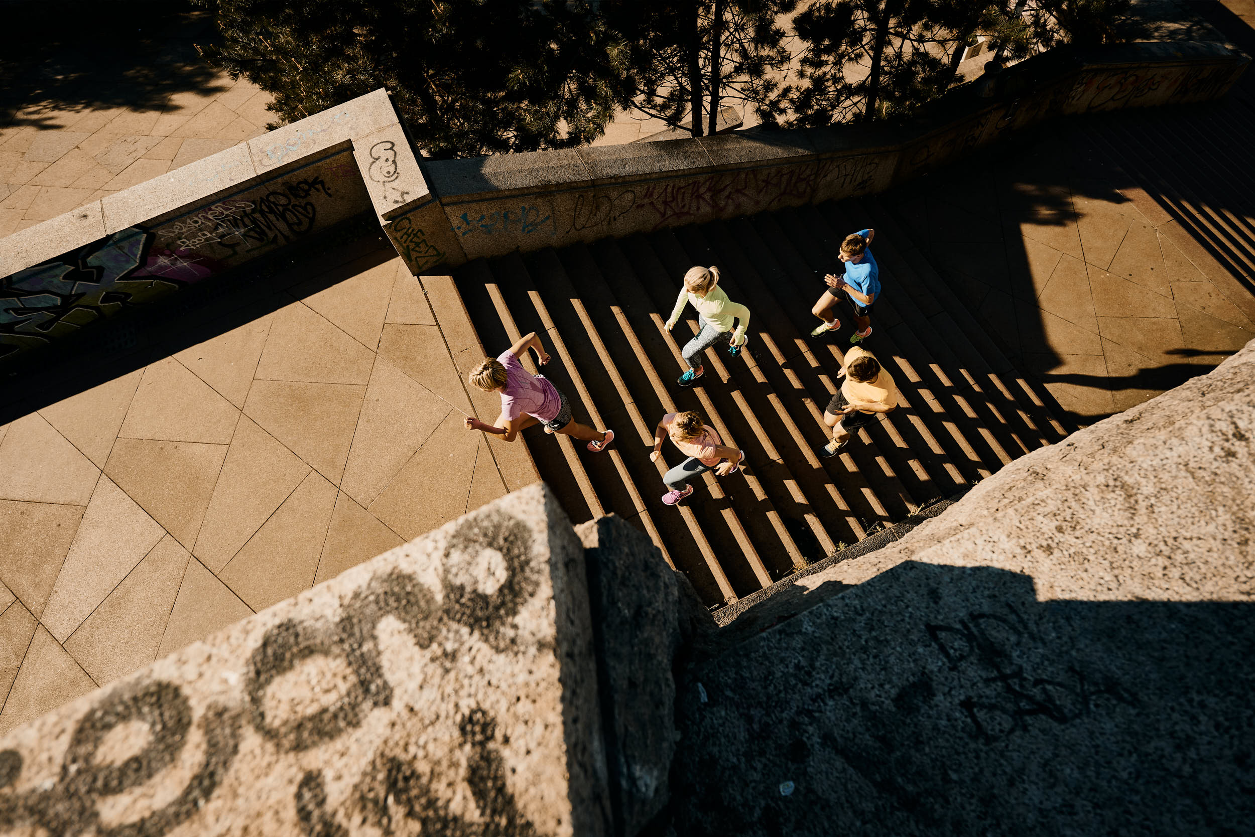 Running campaign photography: group of athletes running up a staircase shot from above.