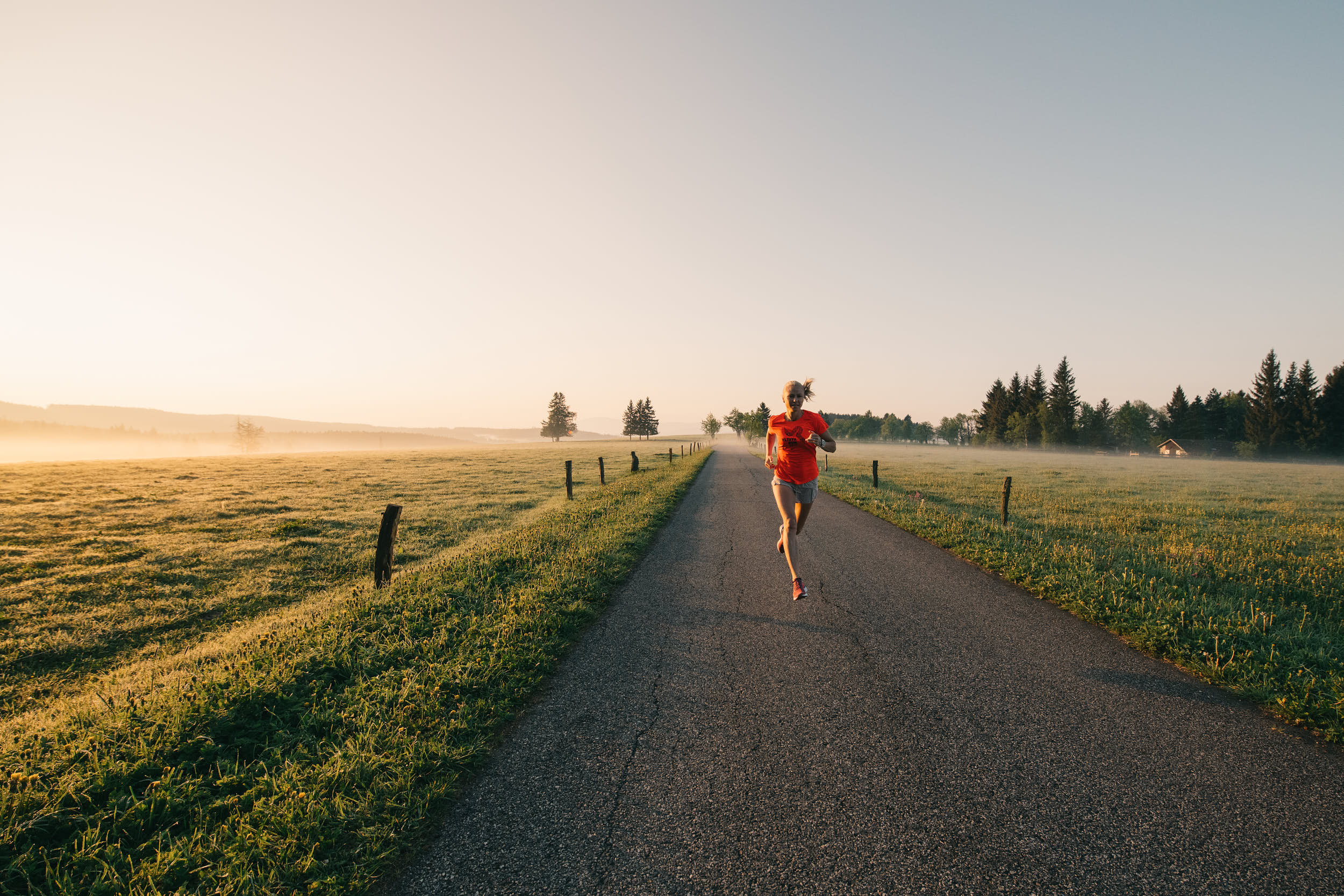 Running apparel campaign: woman running through beautiful landscape at dawn.