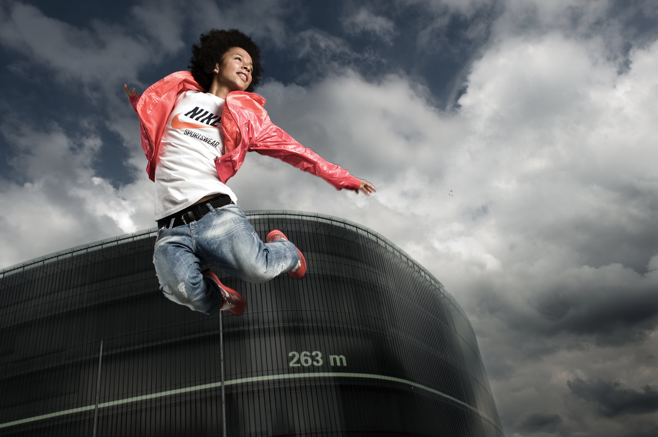 Dancer in sport apparel campaign jumping in front of a modern minimal architecture.