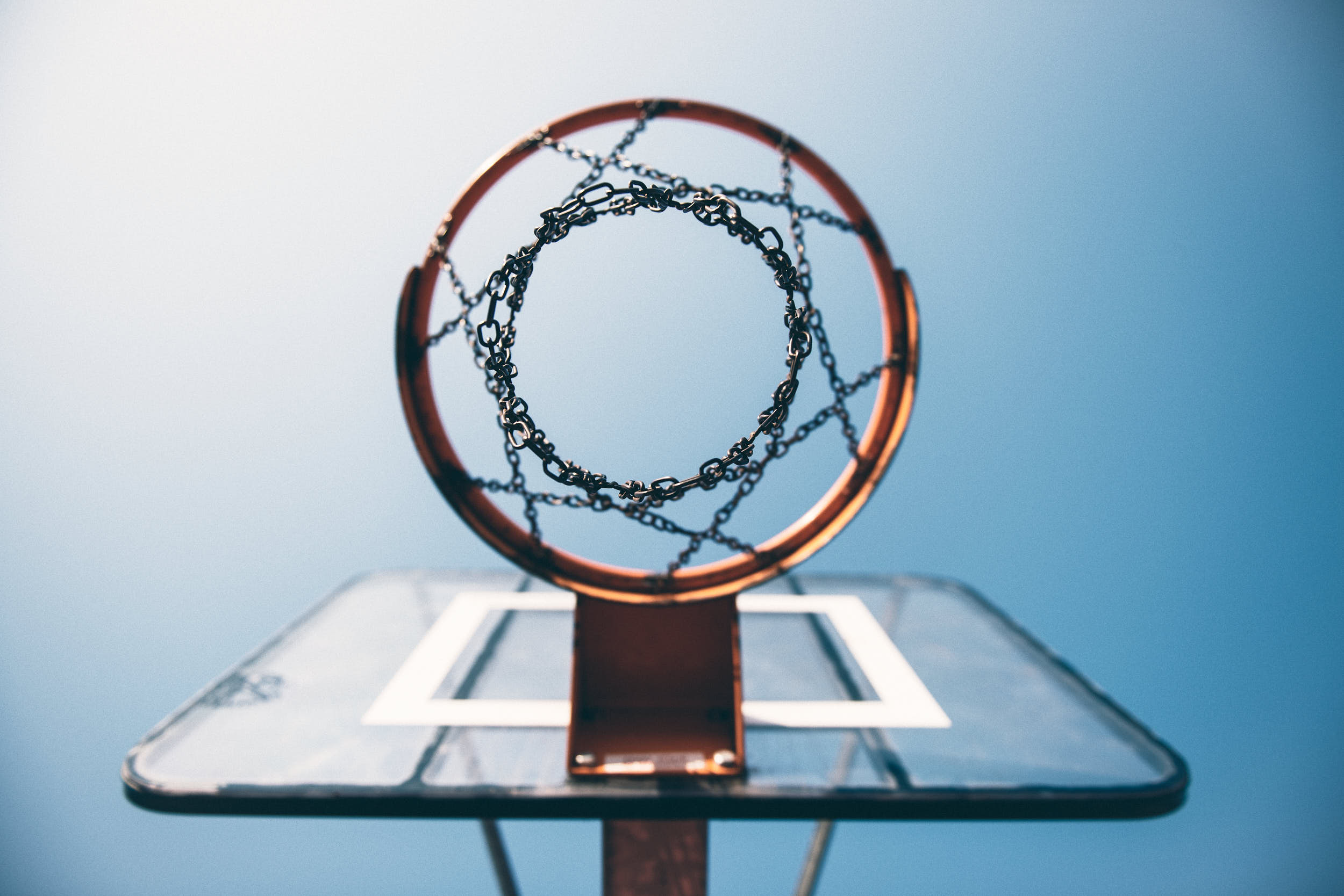 Basketball hoop with a chain net photographed from beneath with blue clear sky.