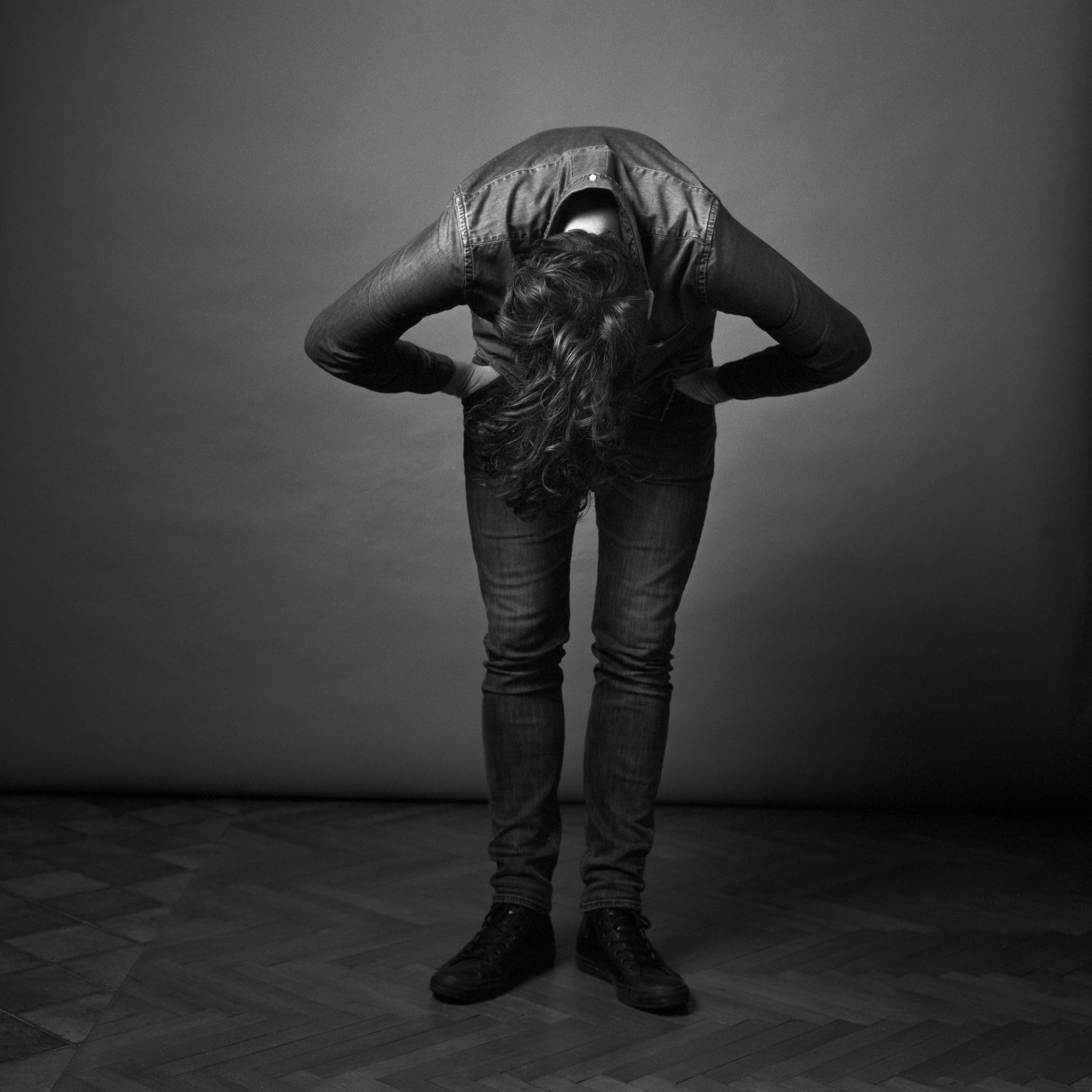 Medium format black and white film photography: man adjusting his hair in front of a grey background