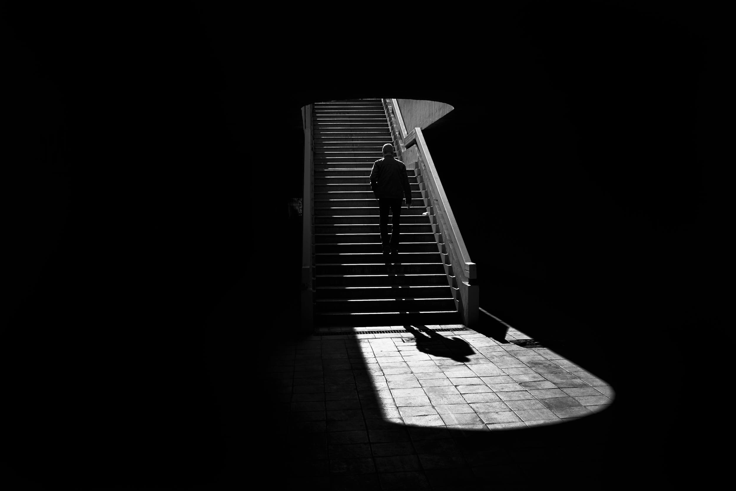 Black and white street photography: man walking up a staircase in an urban scene with deep shadows and strong contrast.