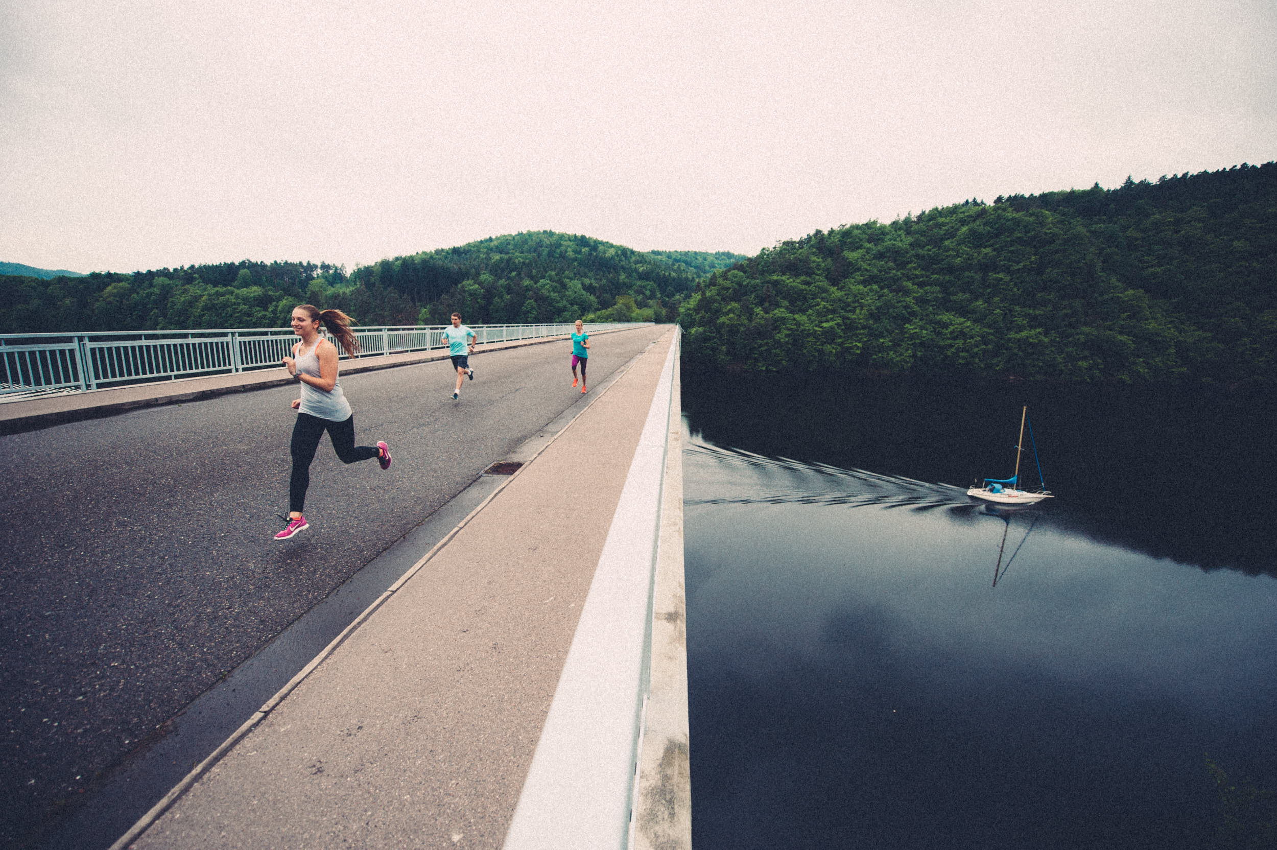 Group of athletes running across a bridge over a dam.
