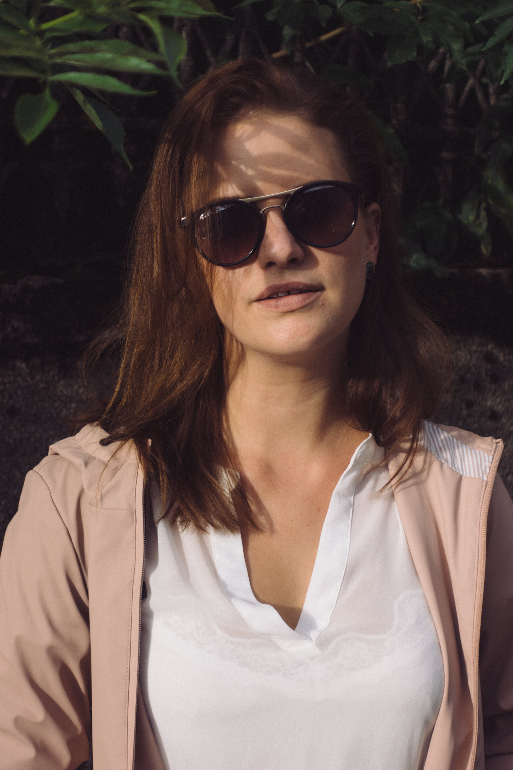 Portrait of a woman in sunglasses with leaves shadows pattern on the face.