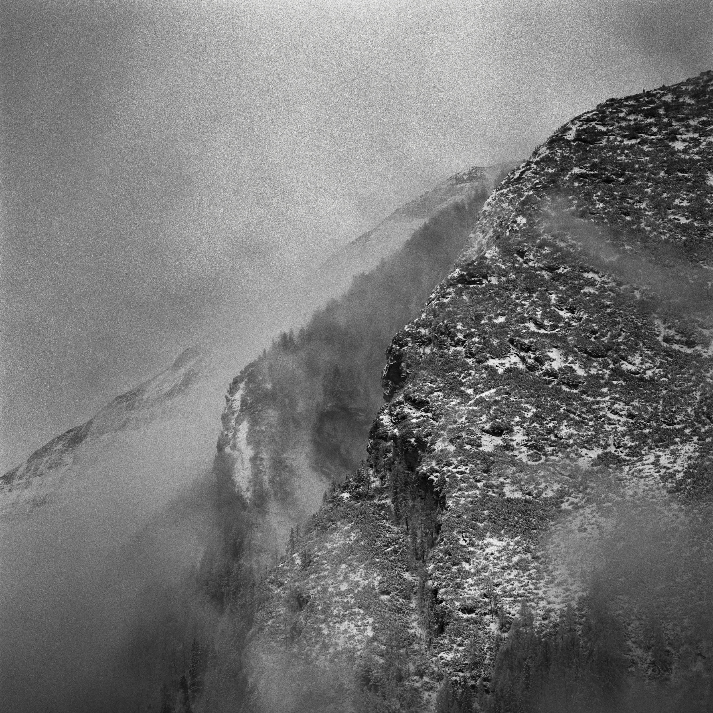 Black and white medium format film photography: detail of a steep mountain in fog.
