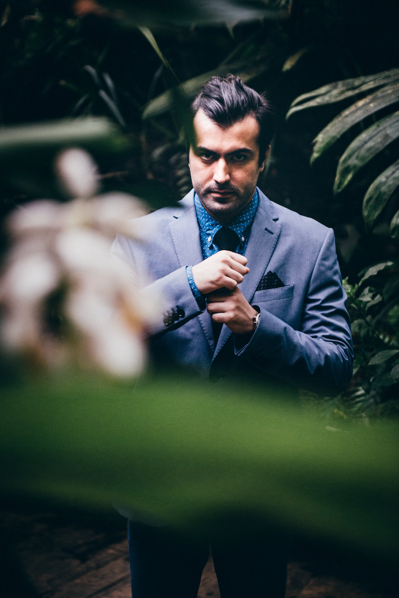 Man adjusting his suit surrounded with green plants.