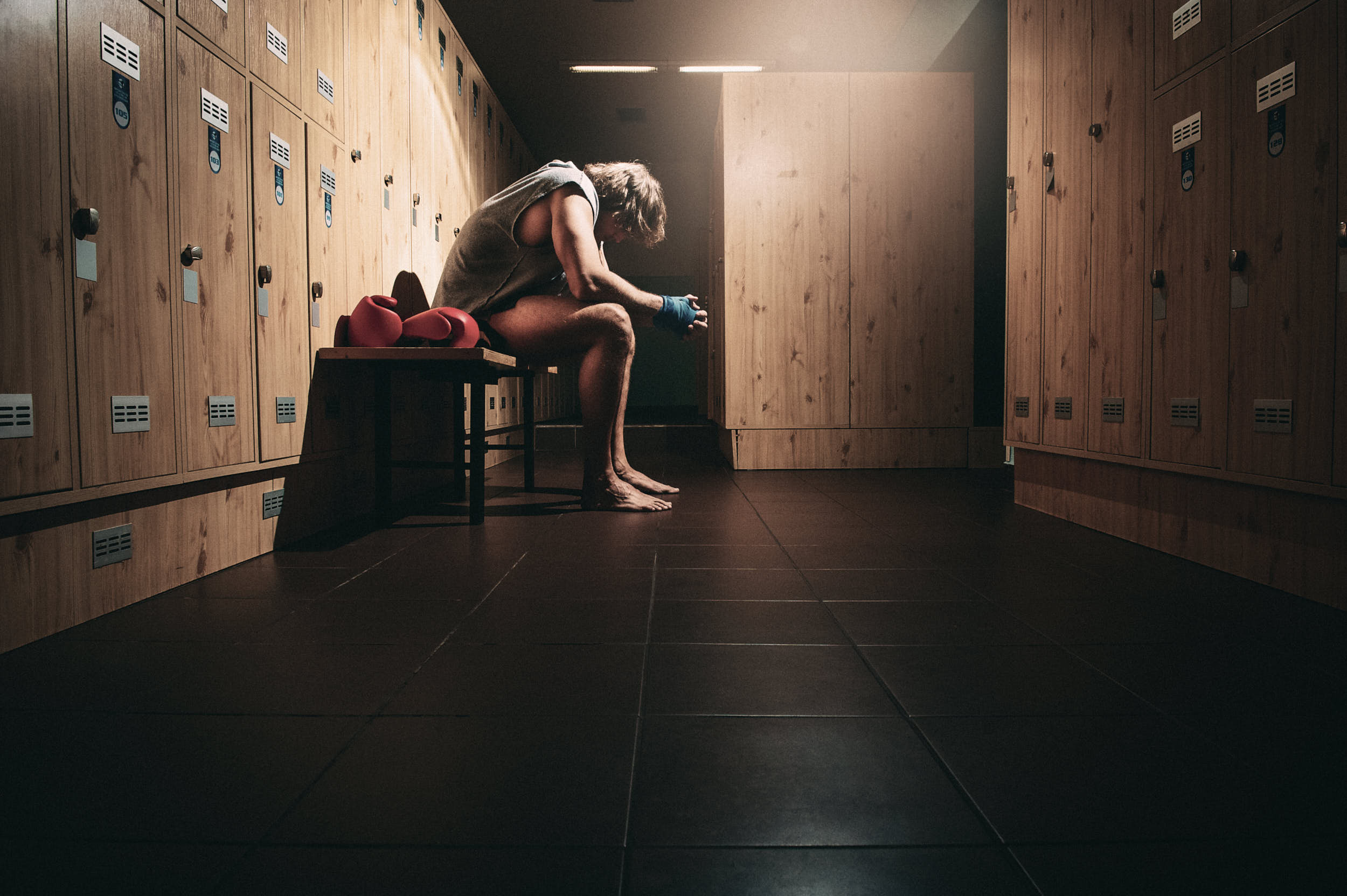 action sports advertising photography: boxer sitting in a locker room preparing for the fight.