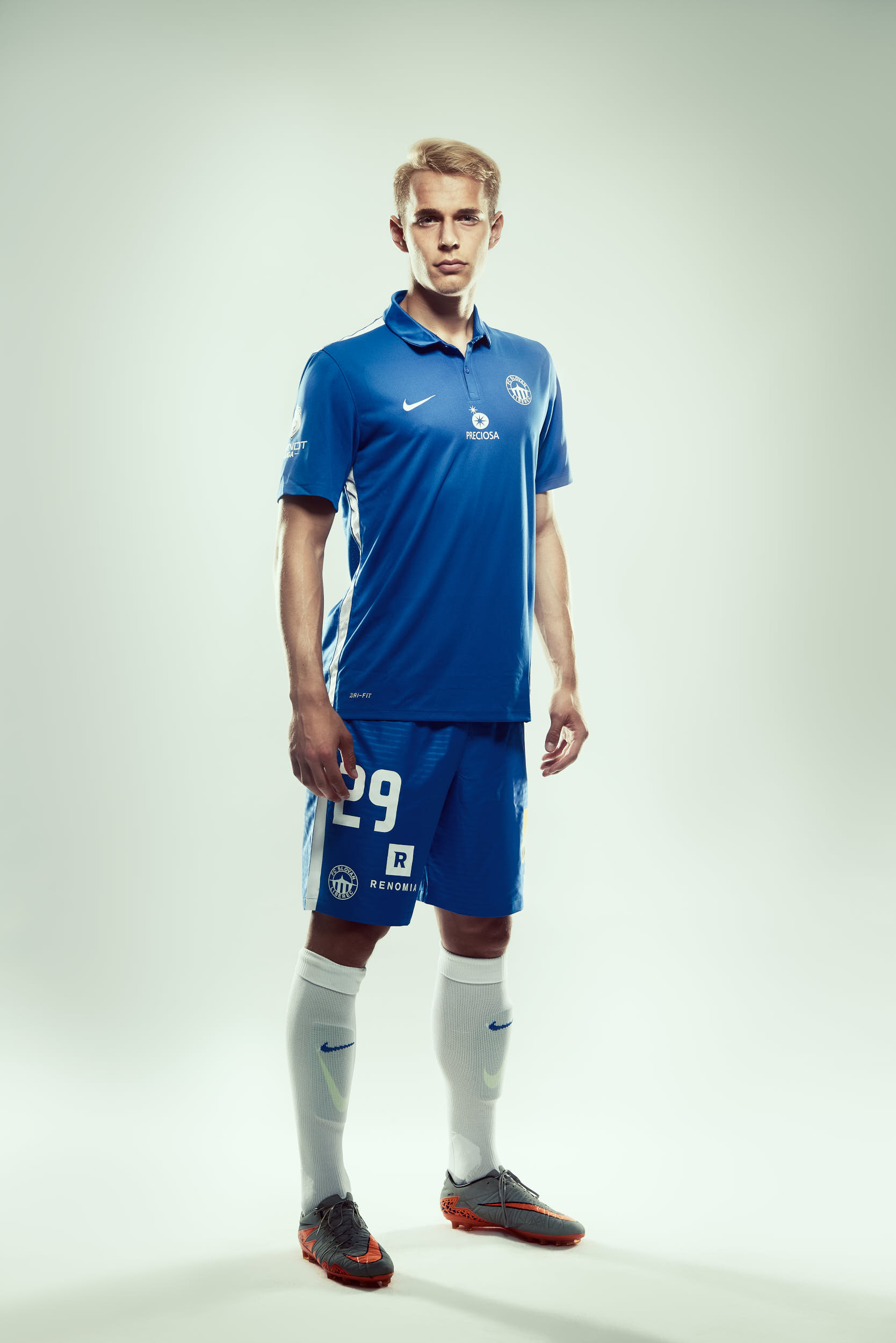 Sports apparel advertising photography: football player posing in a match kit on white background.