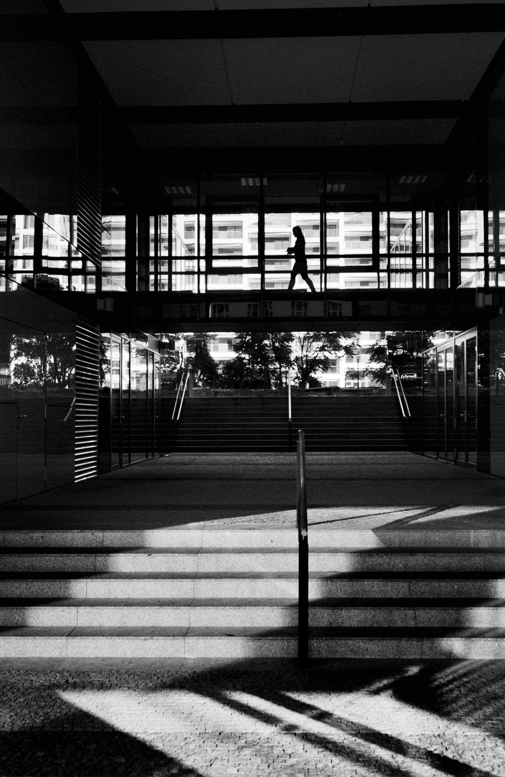 Classic black and white street photography: silhouette of a woman walking through a glass corridor in an office building.