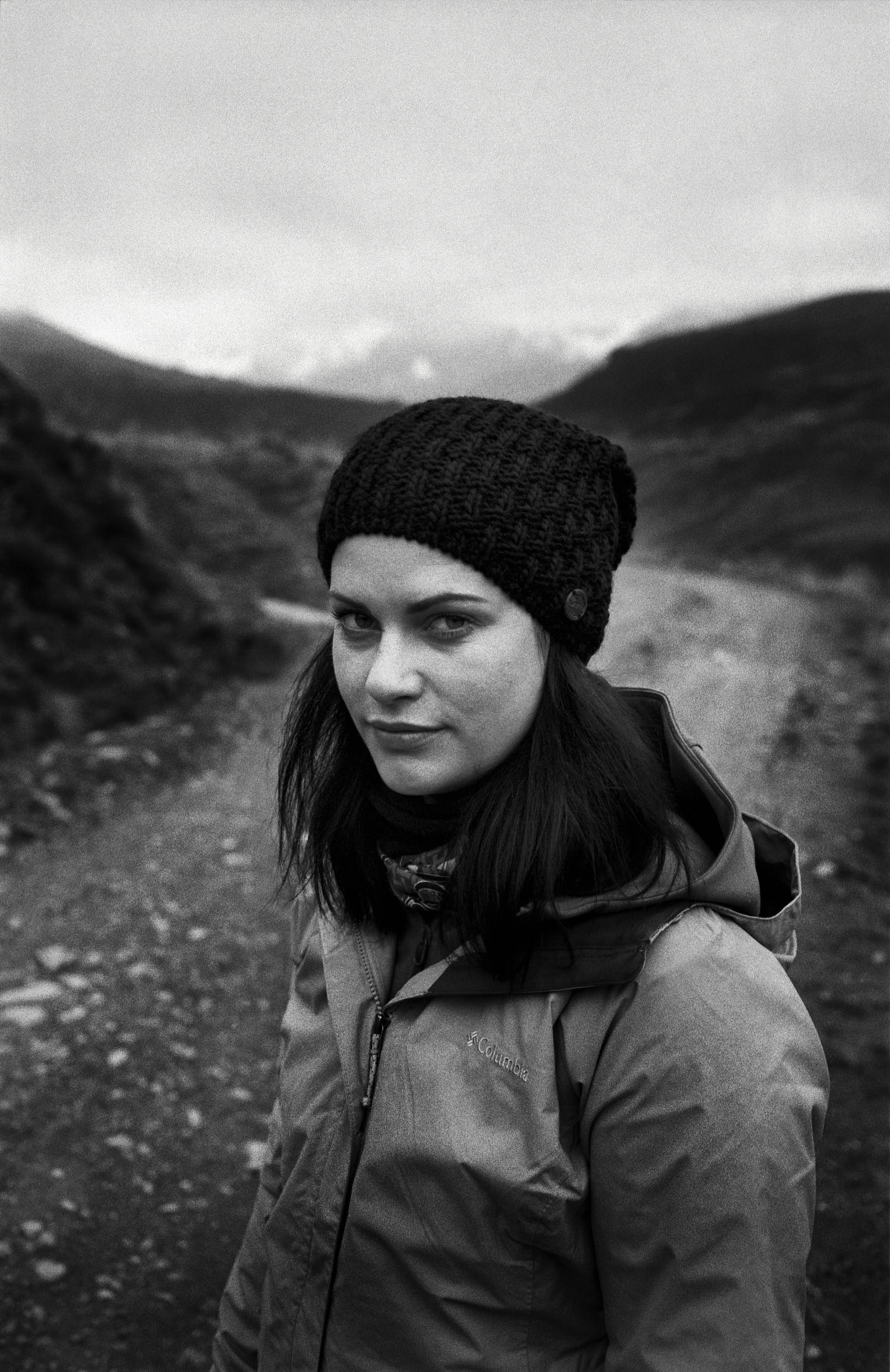 Woman on a mountain path dressed in outdoor apparel in a classic black and white film portrait.