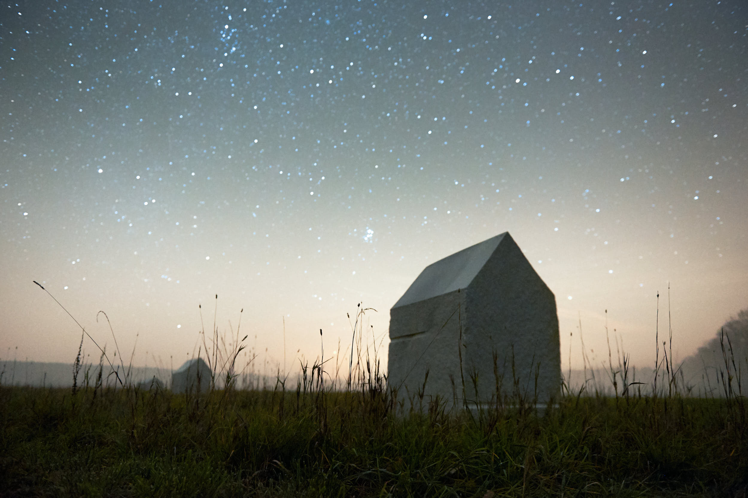 Minimal stone sculptures under starry night sky.