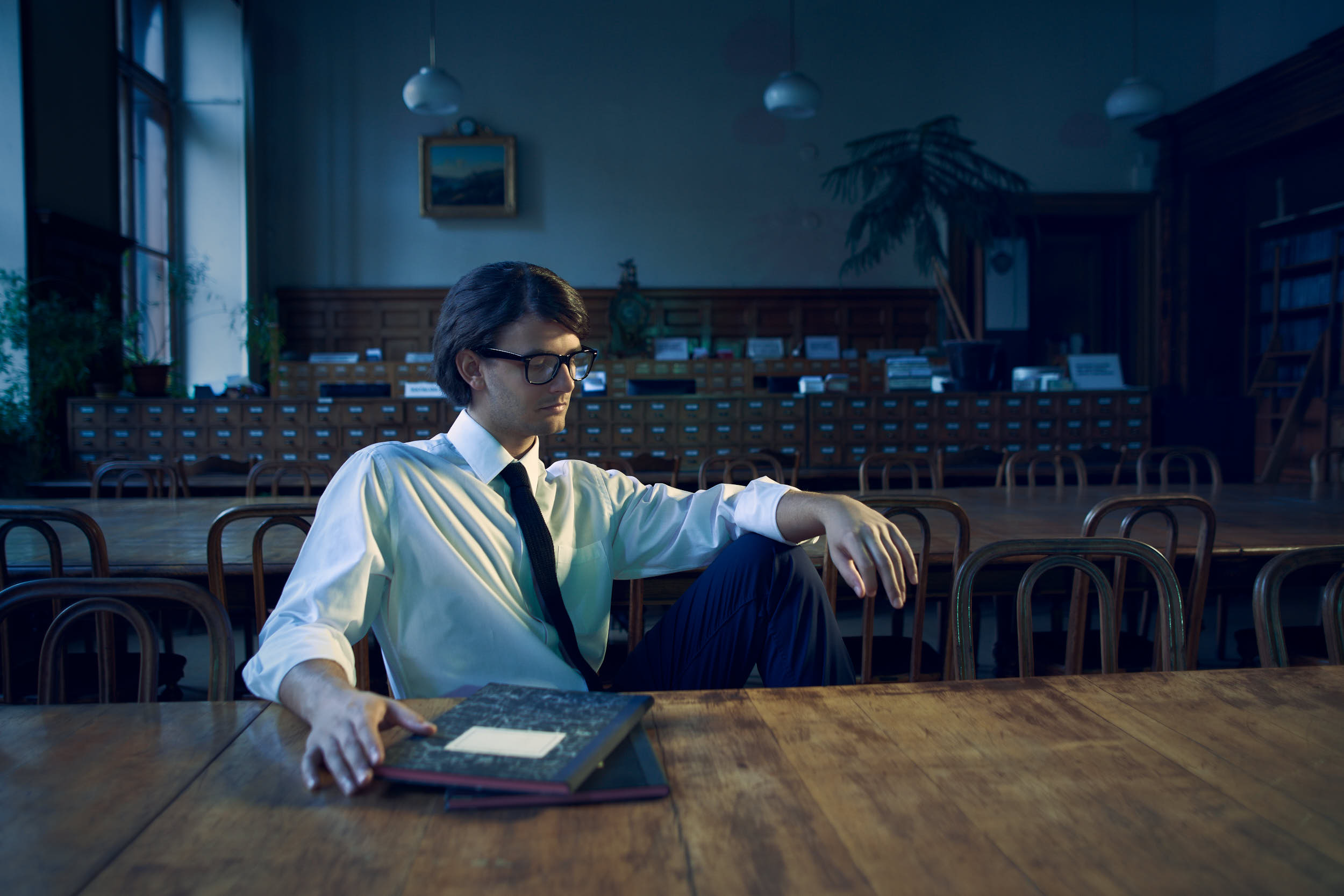 Student with glasses sitting in a library in a cinematic editorial photograph.