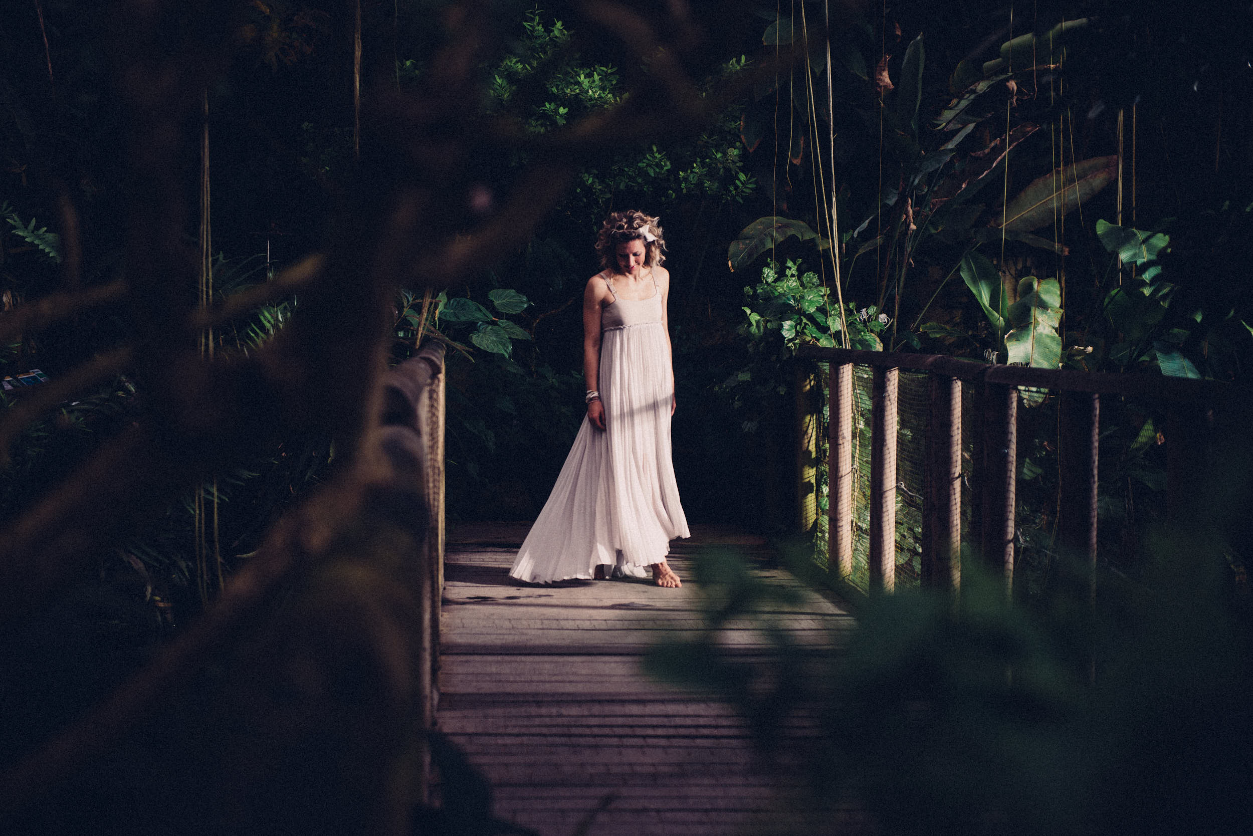 Woman in minimalistic dress walking across a wooden bridge in a jungle-like scene.