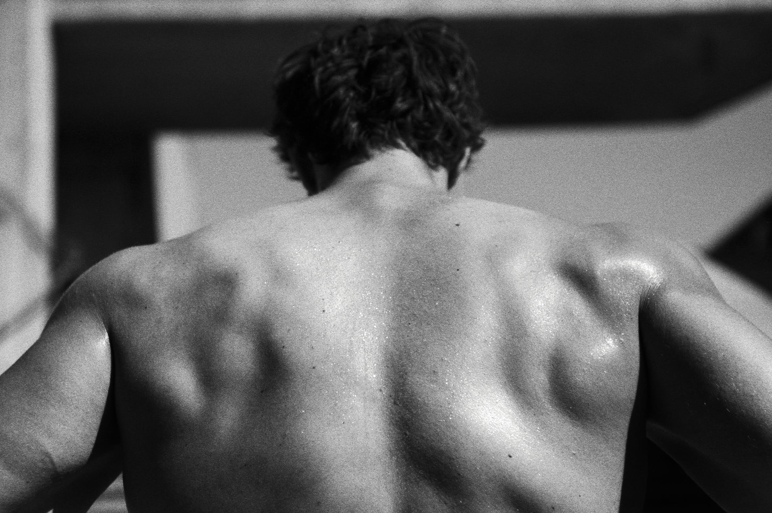 Muscular back of a fitness athlete in a black and white sport advertising photography.