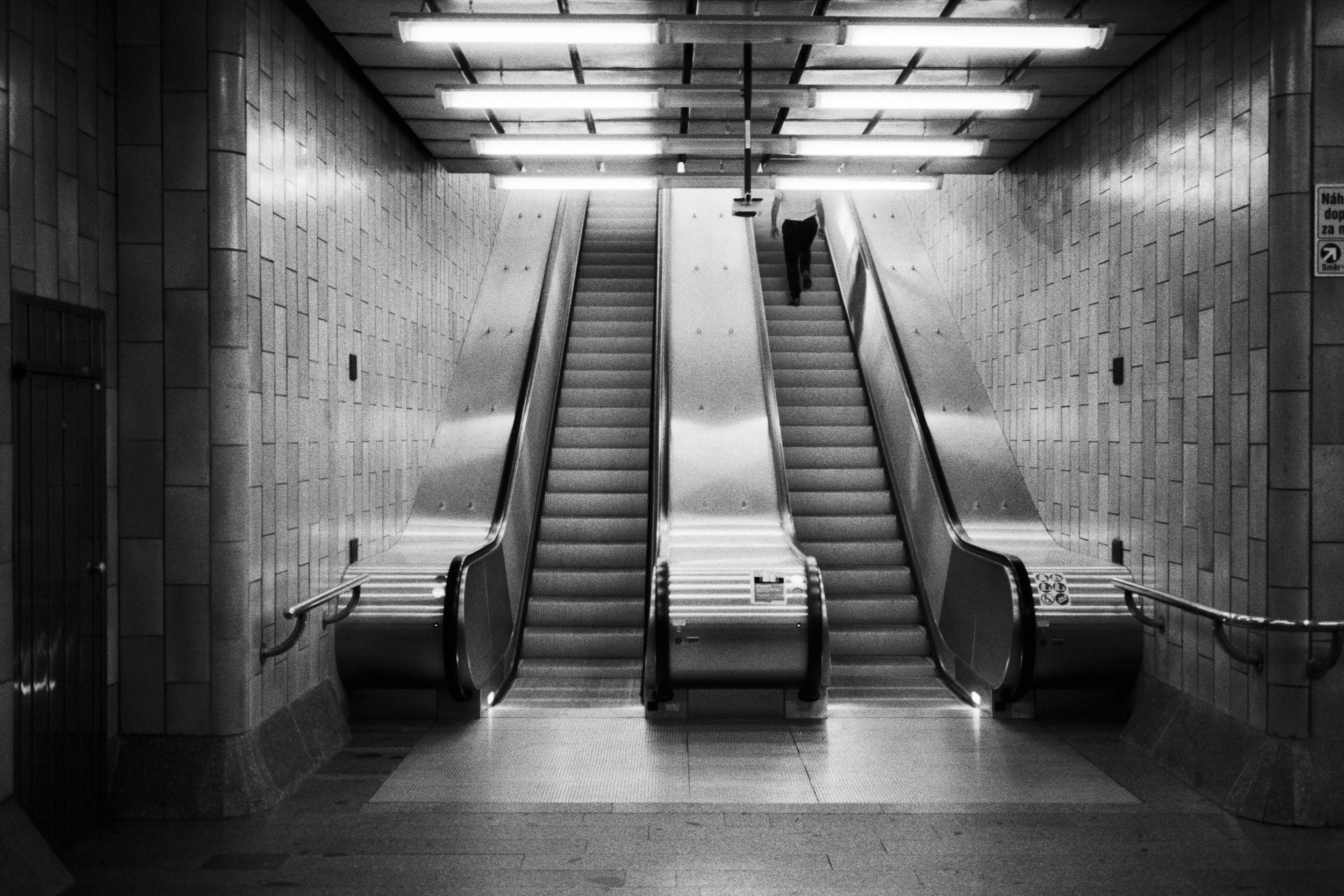 Black and white street photography: underground station escalator with solitary person riding up.