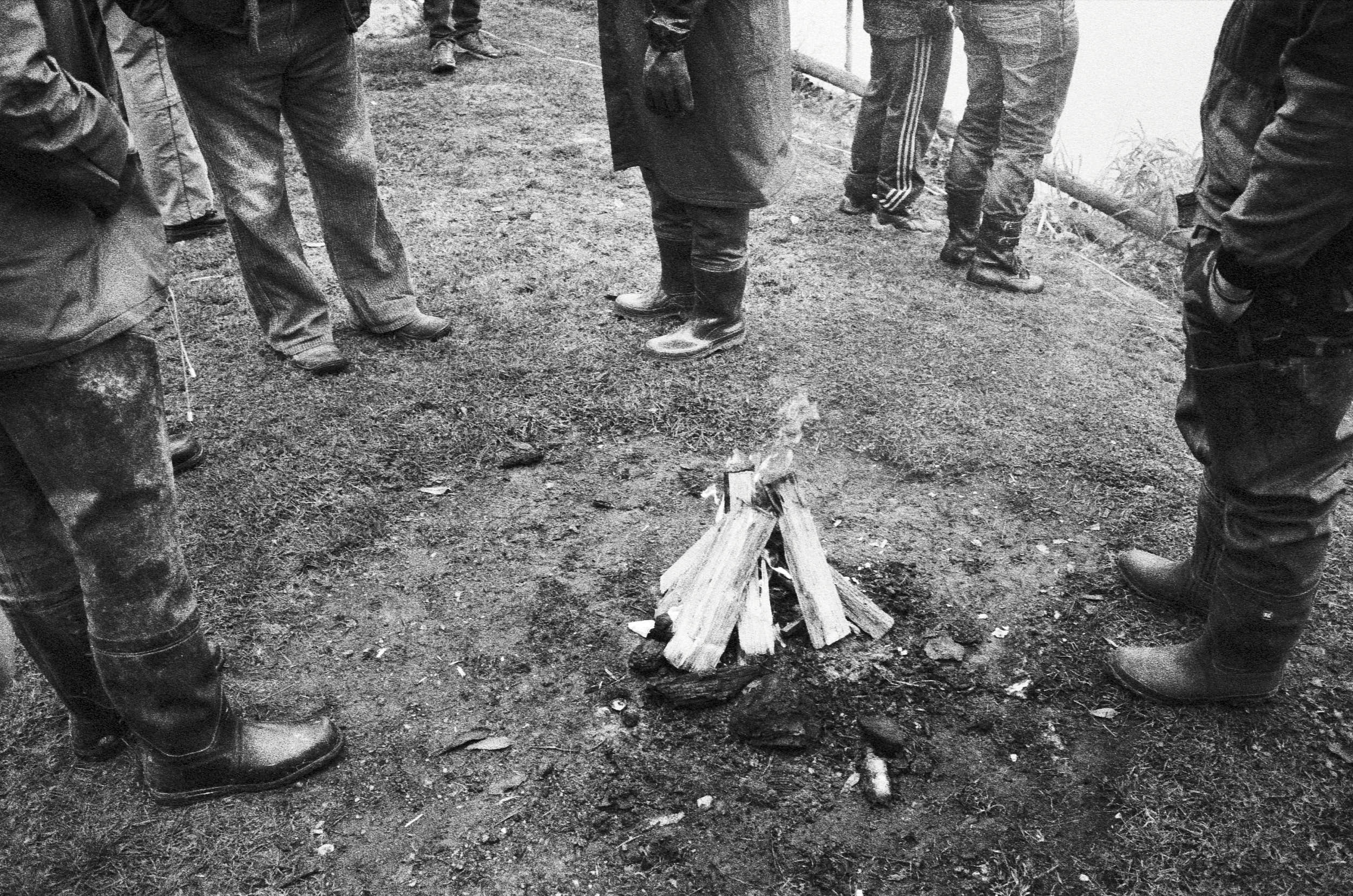 Group of people in wellington boots gathering around a campfire in a black and white documentary photograph.