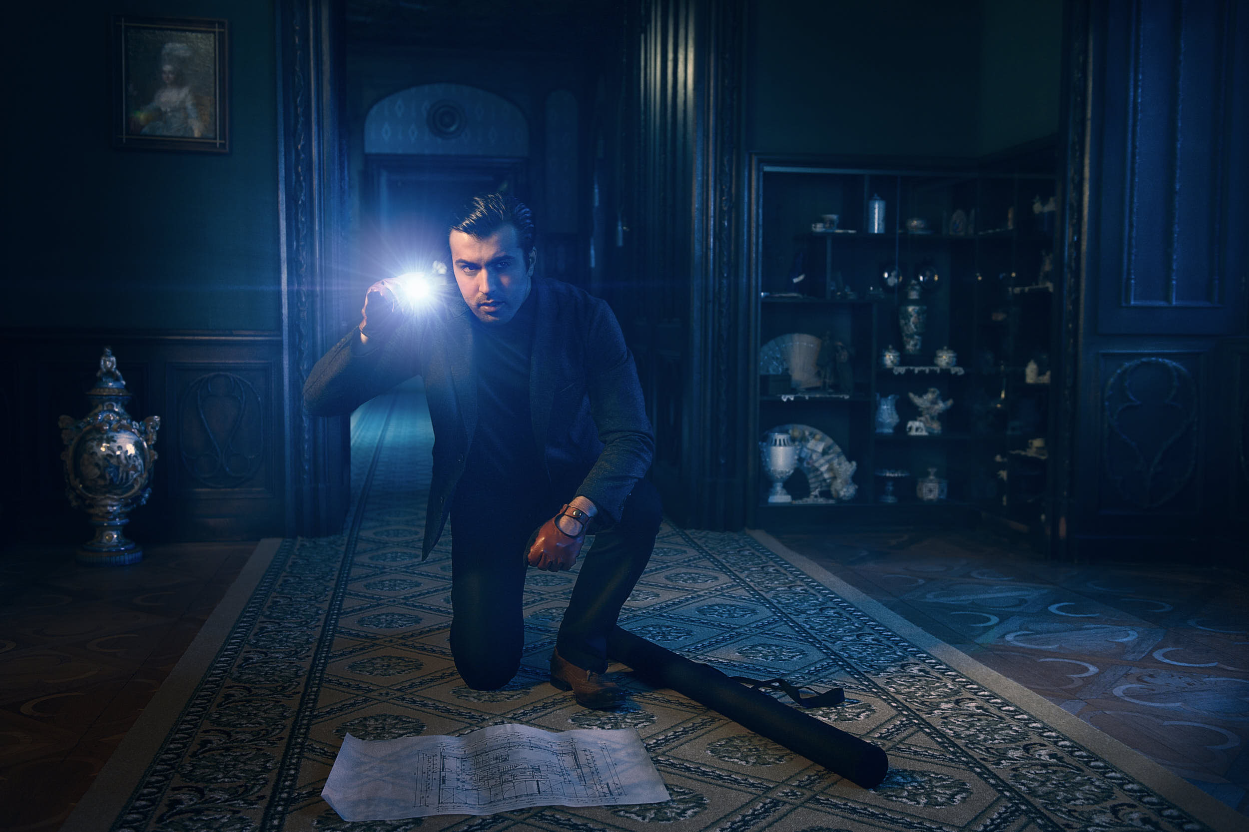 Cinematic editorial photography: a thief with a flashlight is preparing to rob a castle.