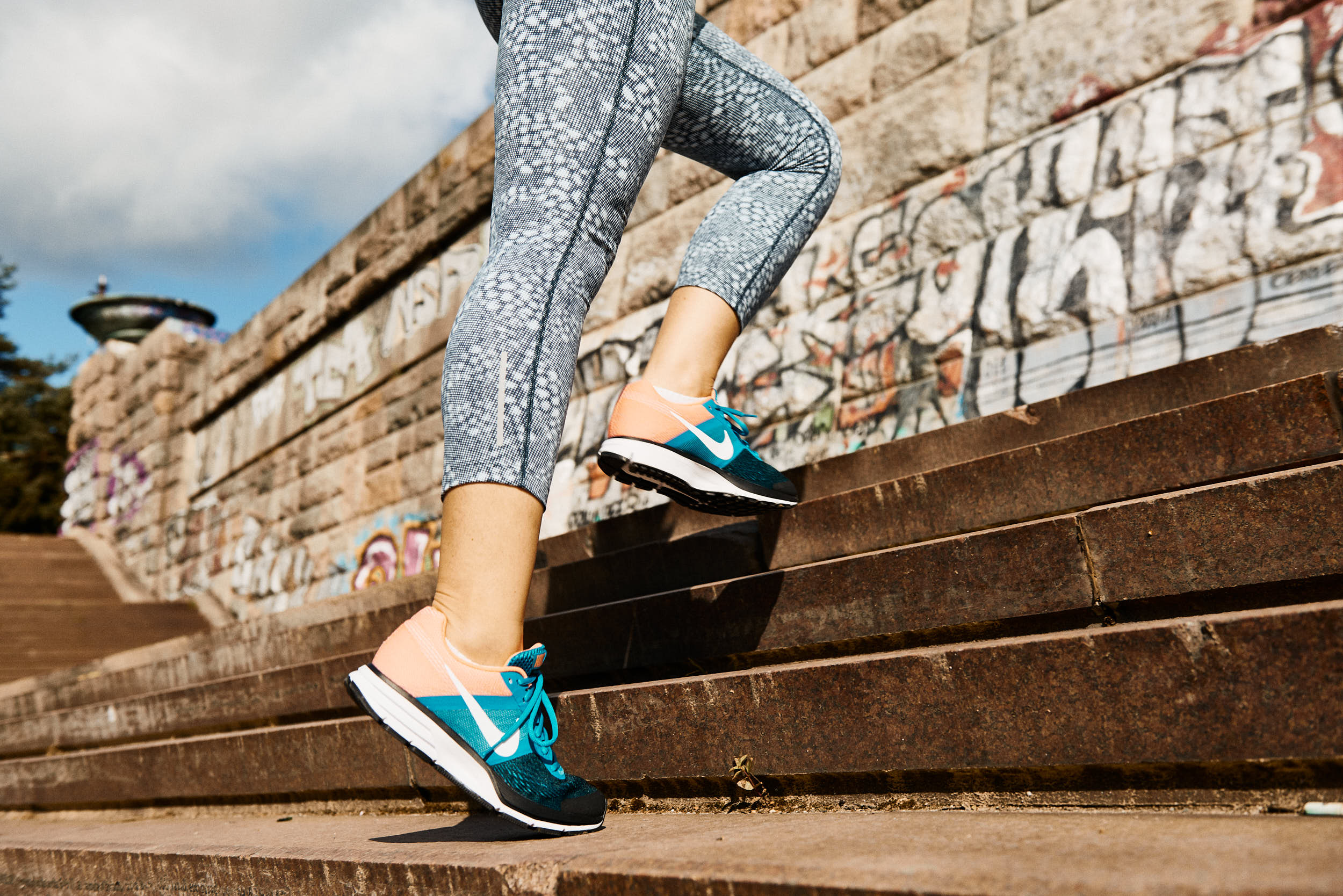 Running apparel advertising photography: detail of a girl in running shoes on stairs.