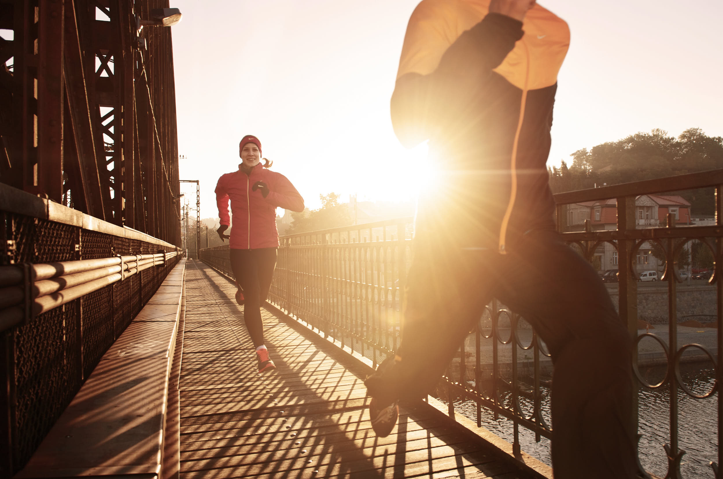 Couple running across a railway bridge at sunrise.