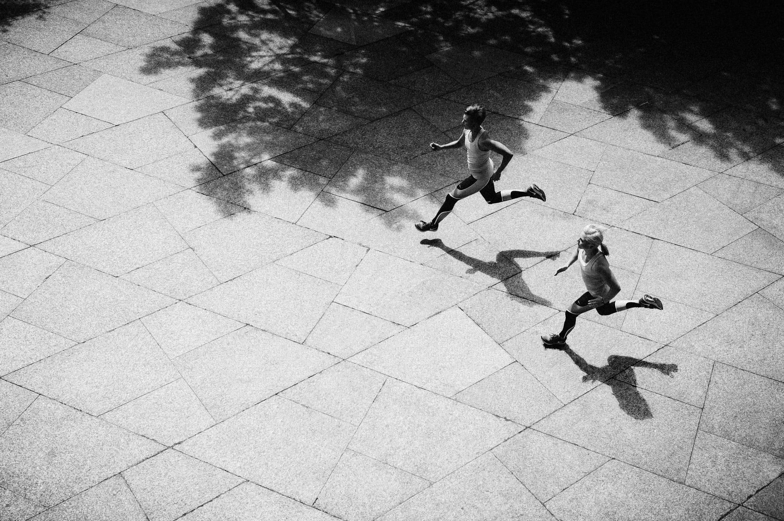 Black and white sport photography: two girls running on marble pavement shot from elevated perspective with strong contrast.