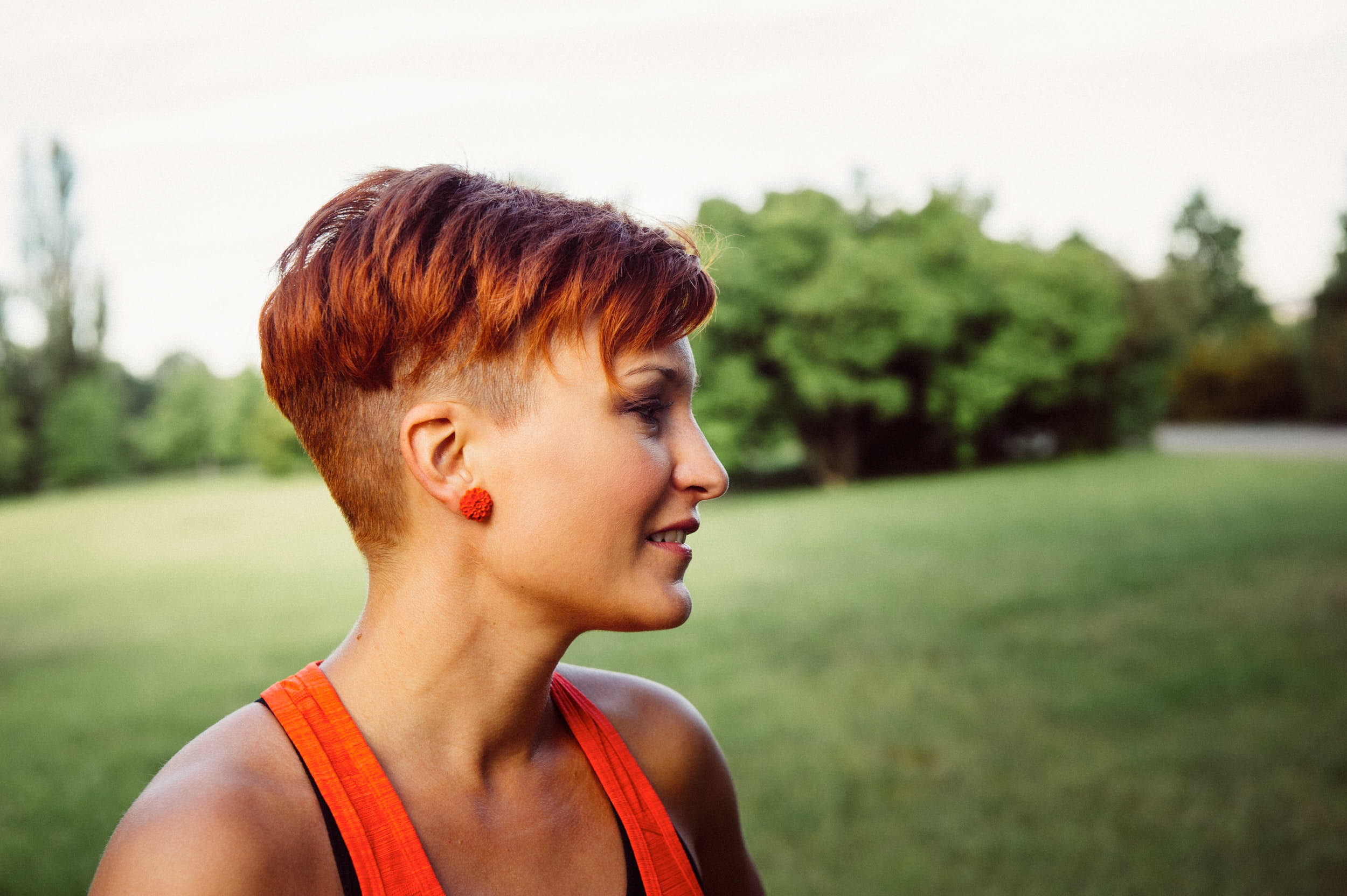 A girl with orange hair and tank top is preparing herself for a run.