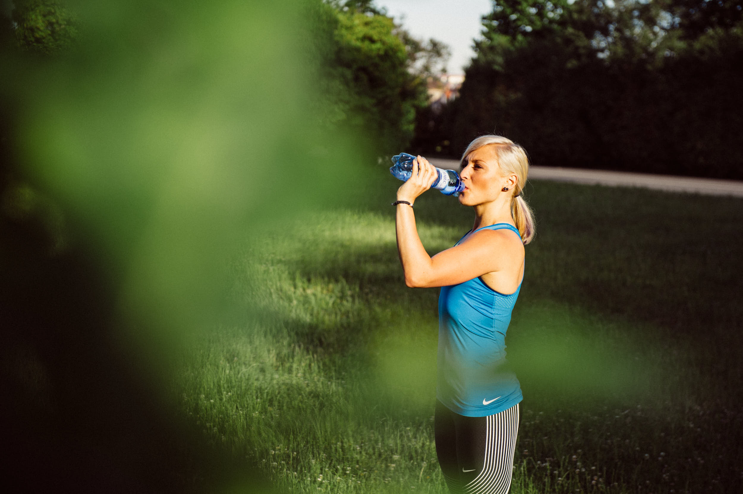 Active lifestyle photography: girl drinking from a water bottle after a workout.