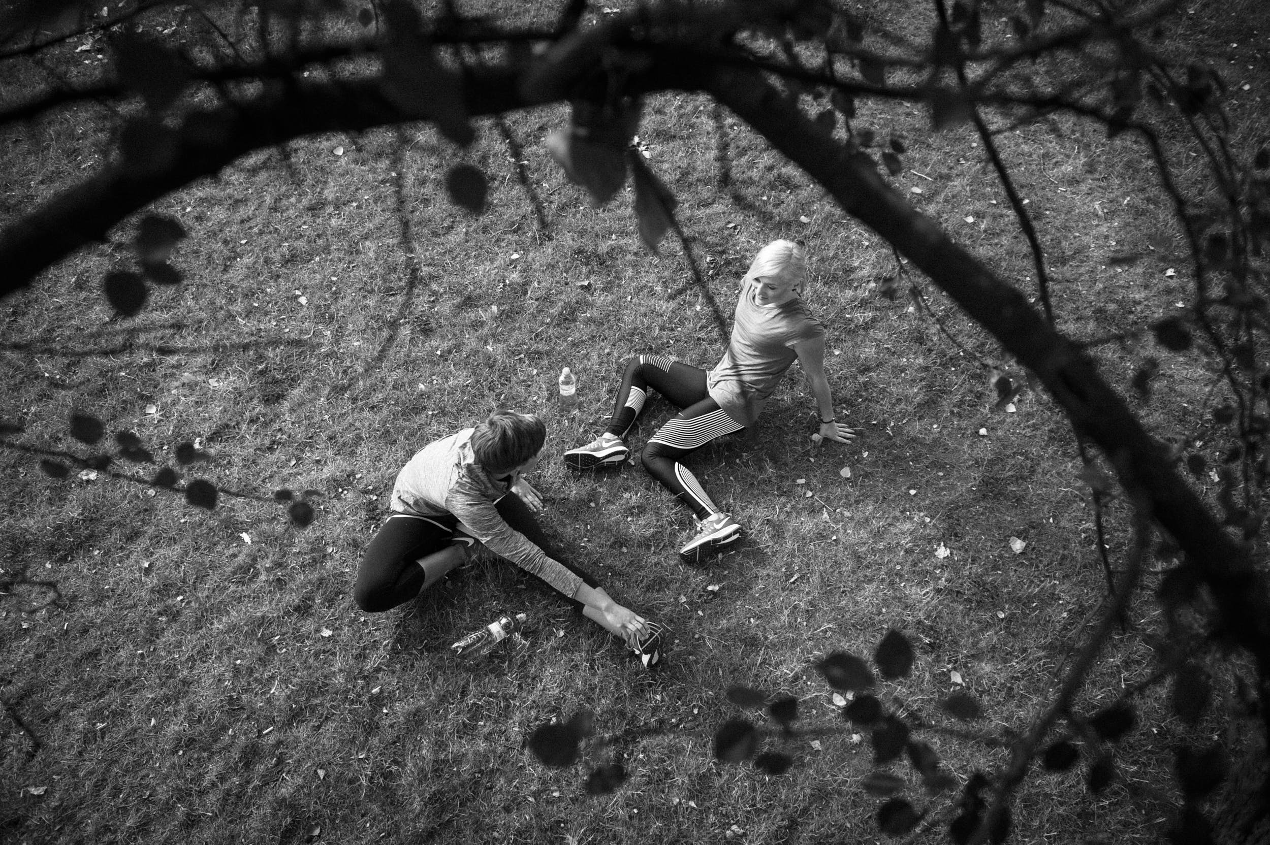 Sports photography: two girls stretching after a run. Shot from elevated perspective with tree branches in the picture.