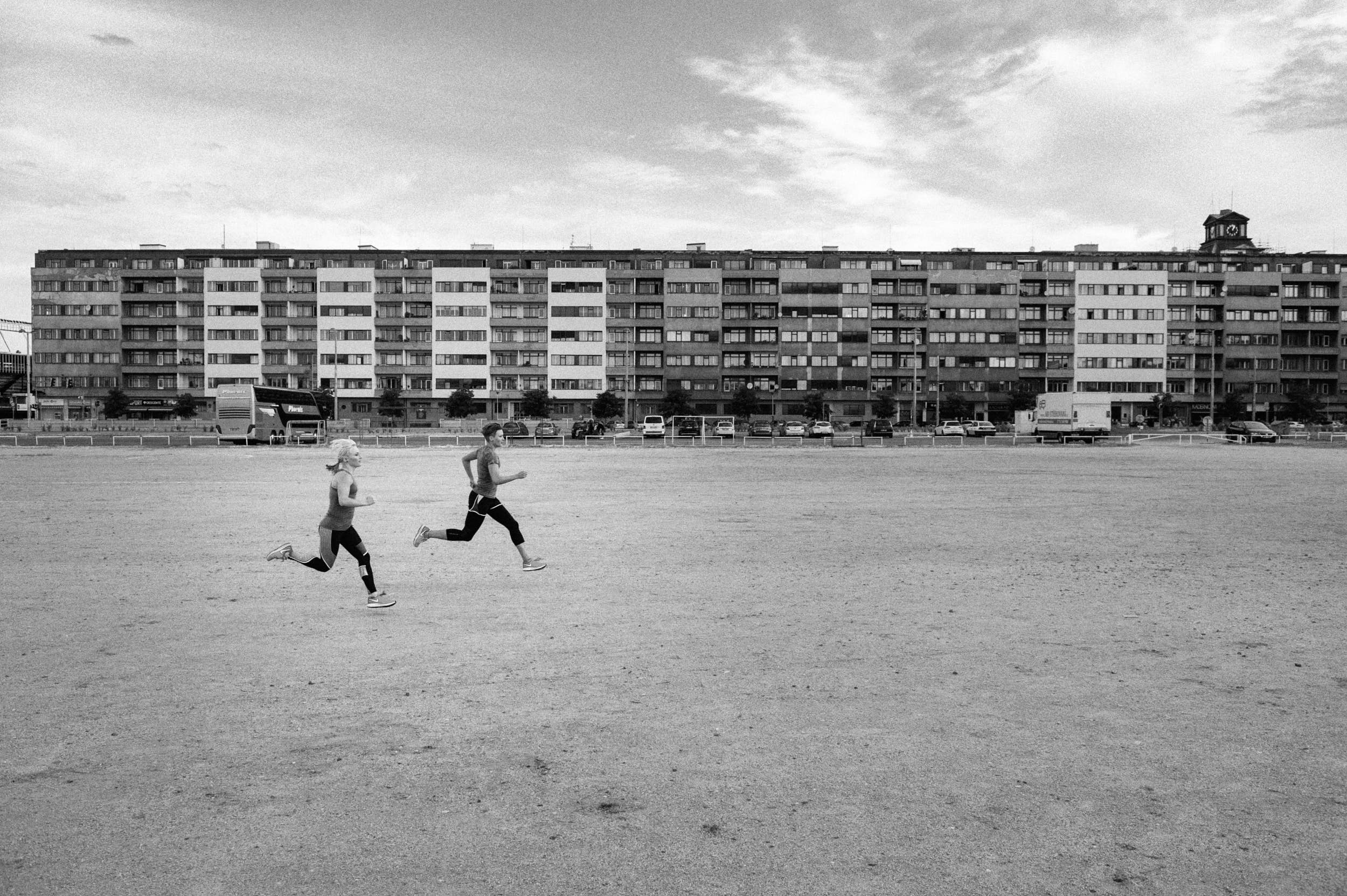 Black and white sport photography: two girls running across a sand plain with big housing estate in the background.