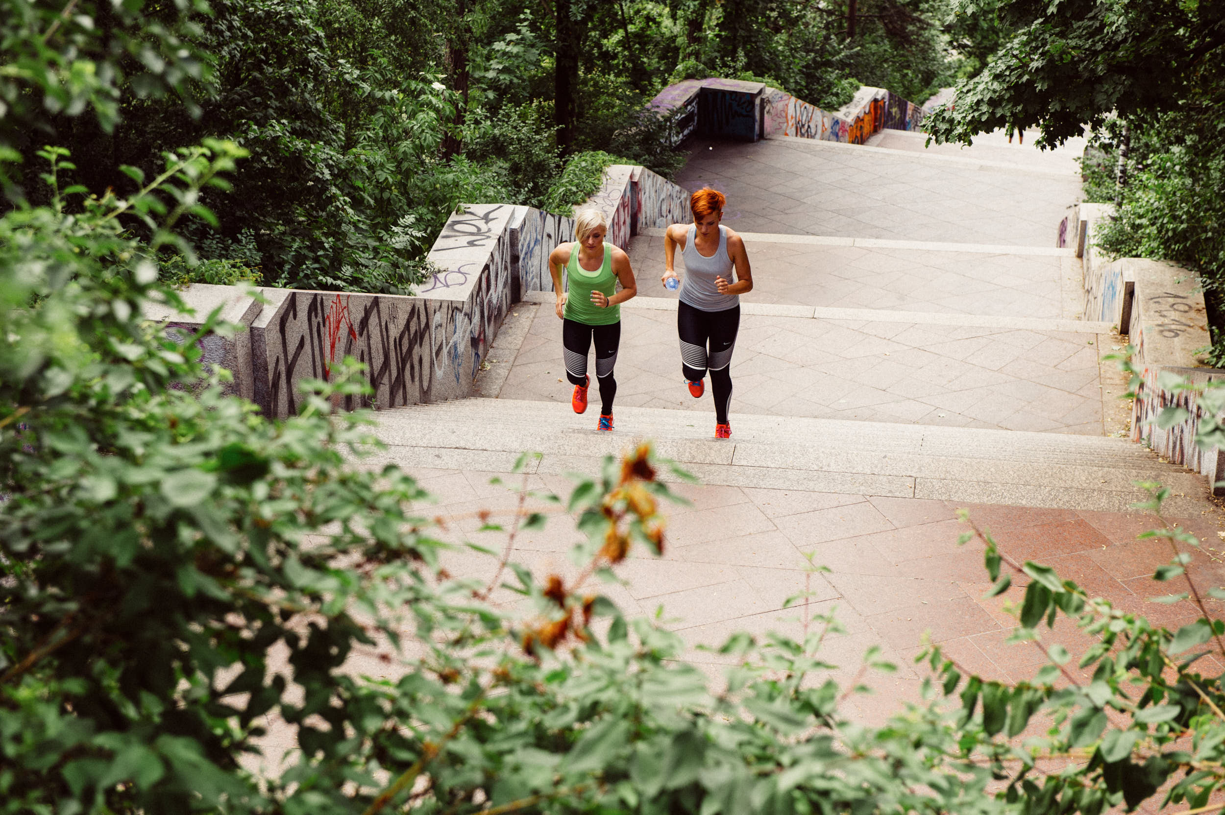 Active lifestyle photography: two girls running up a staircase in a city park.