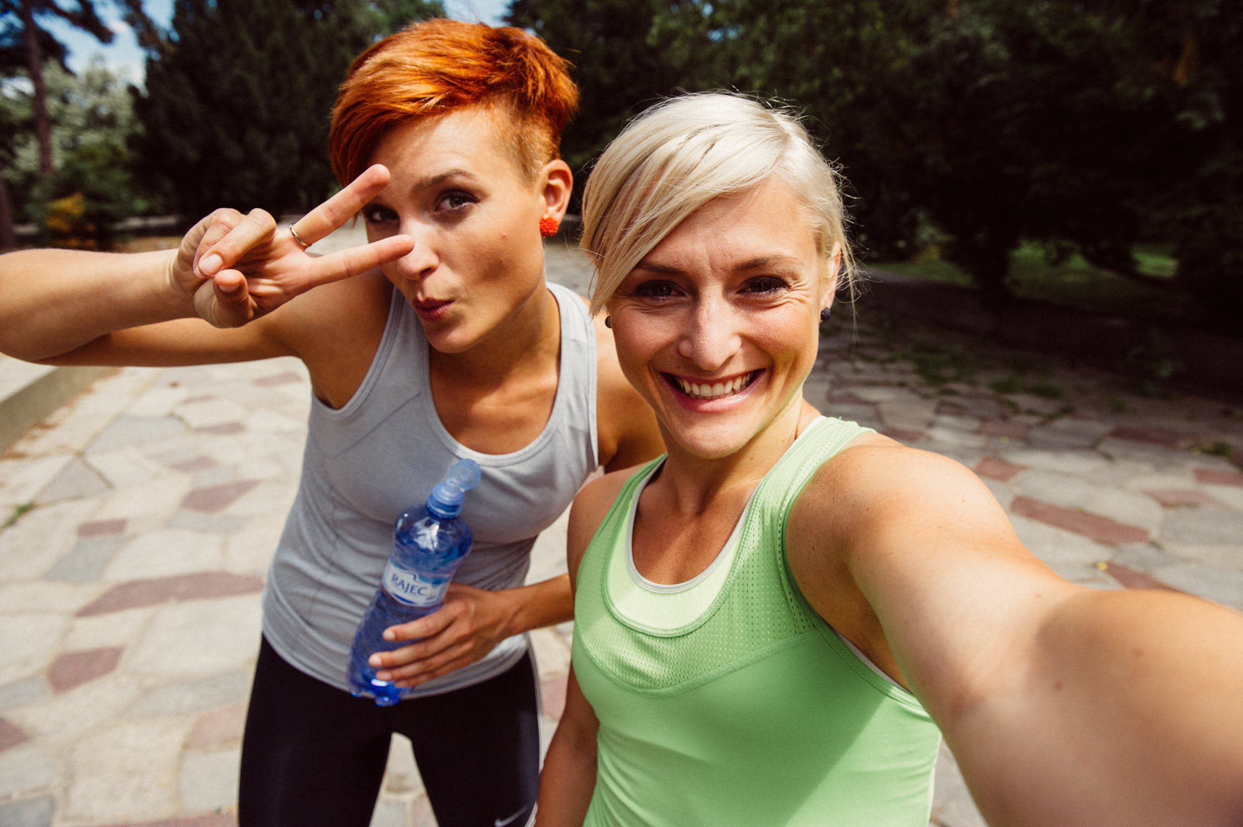 Active lifestyle photography: two female runners in fitness apparel taking a selfie after a workout.