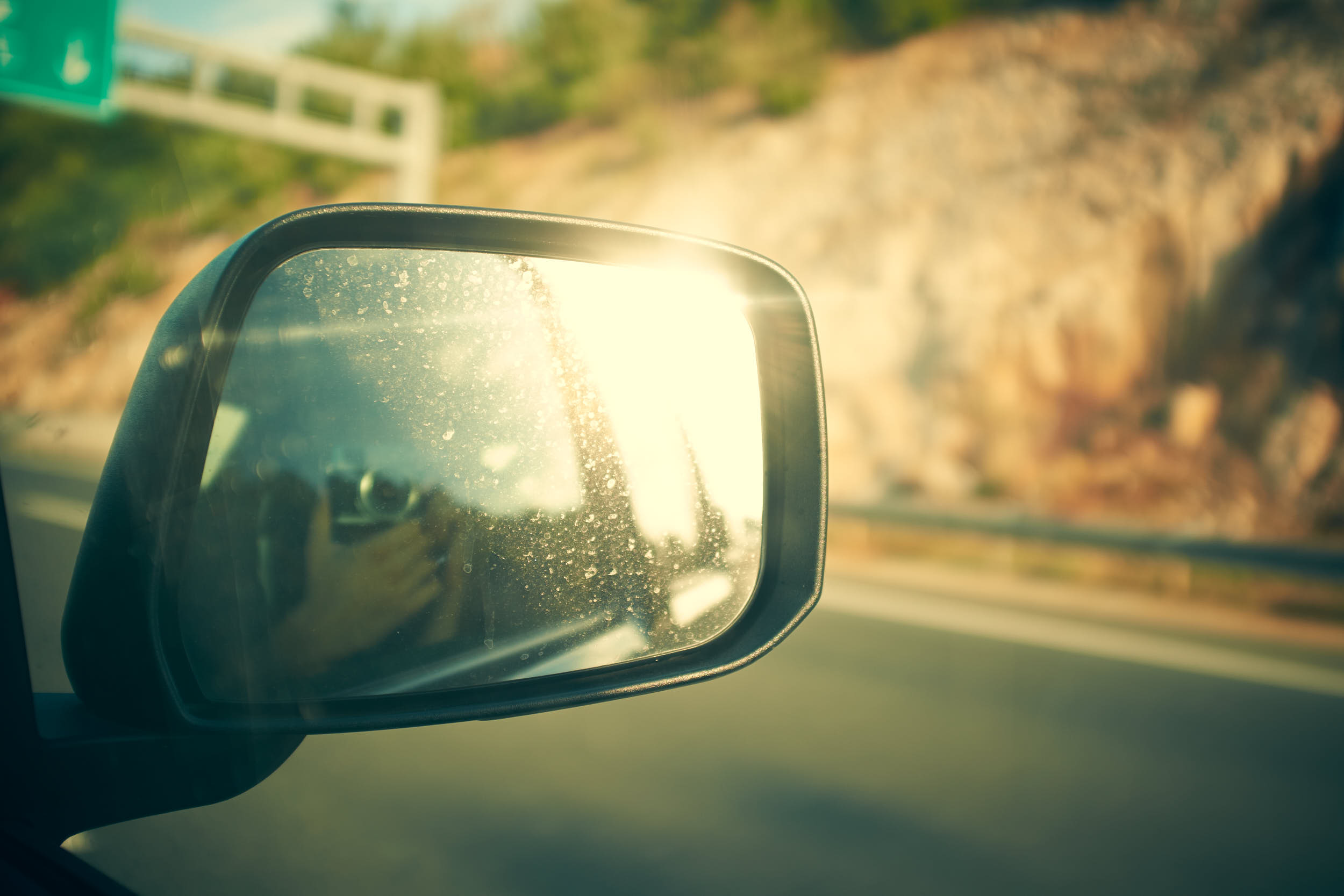 Travel photography on the road. Rearview mirror reflecting sun flare with blurry highway in the background.