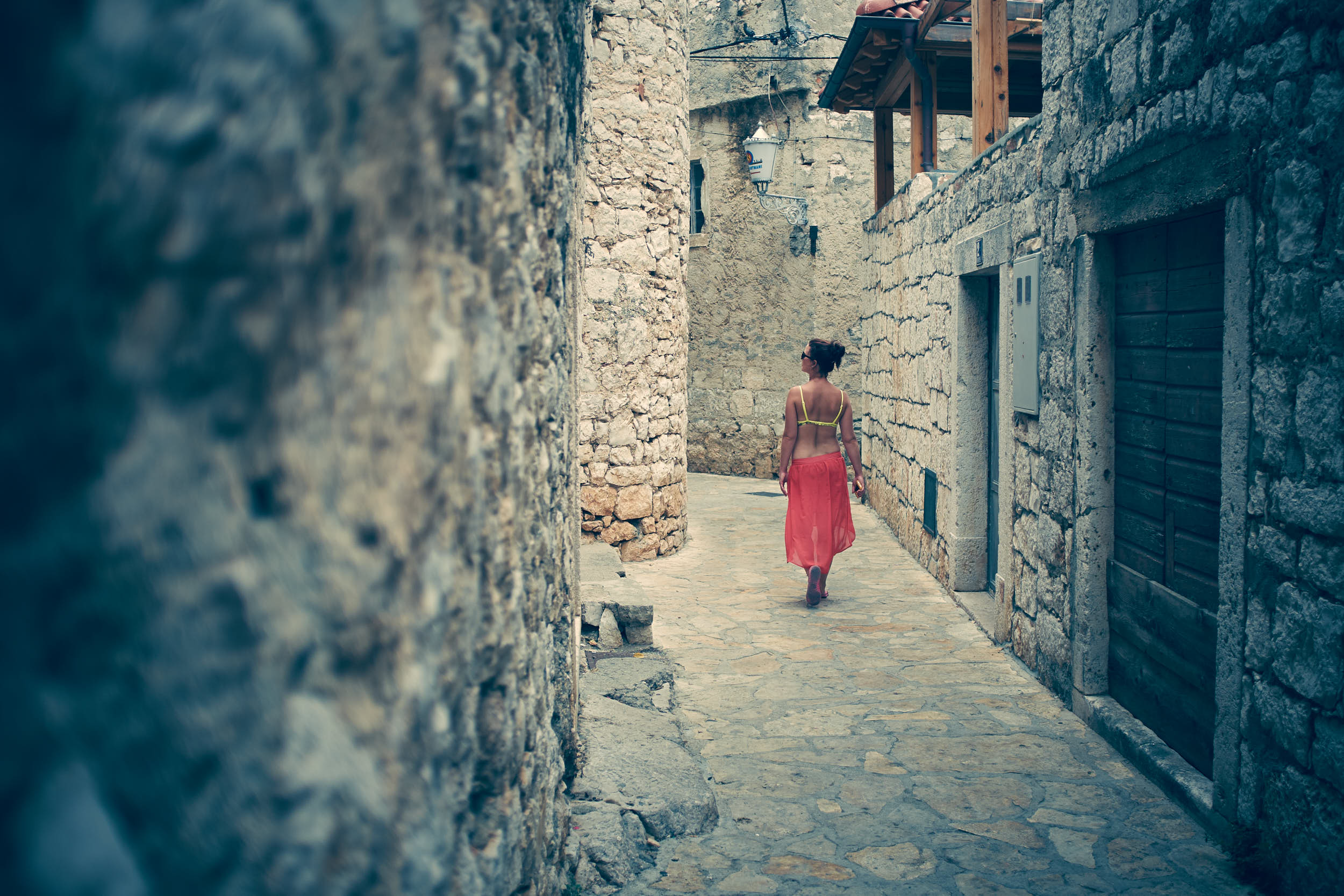 Travel photography: woman wandering through narrow ancient streets of a croatian town.