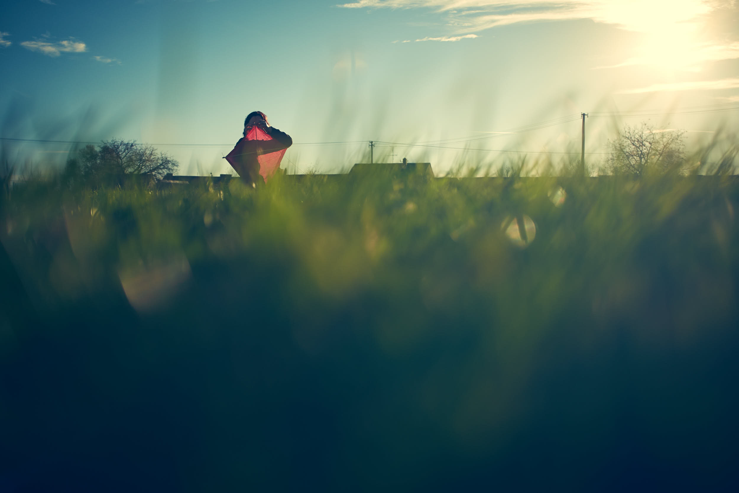 Girl sitting on a meadow is assemling a kite during golden hour.