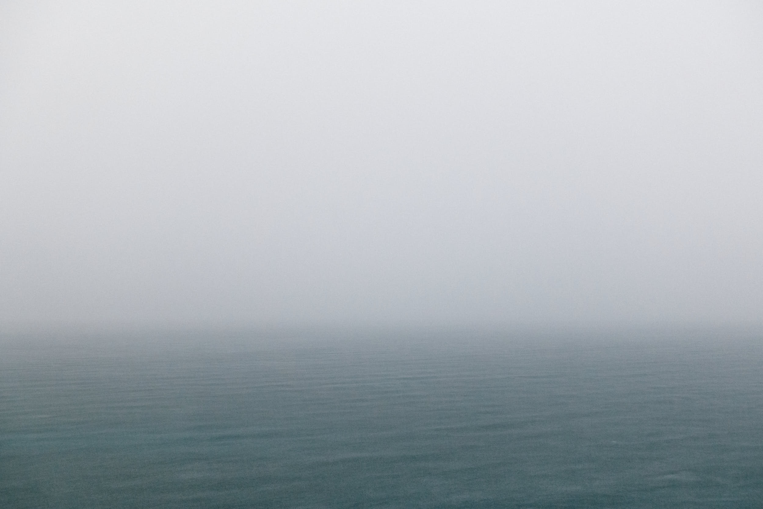 Dramatic minimal seascape during a storm with cool and muted colors.