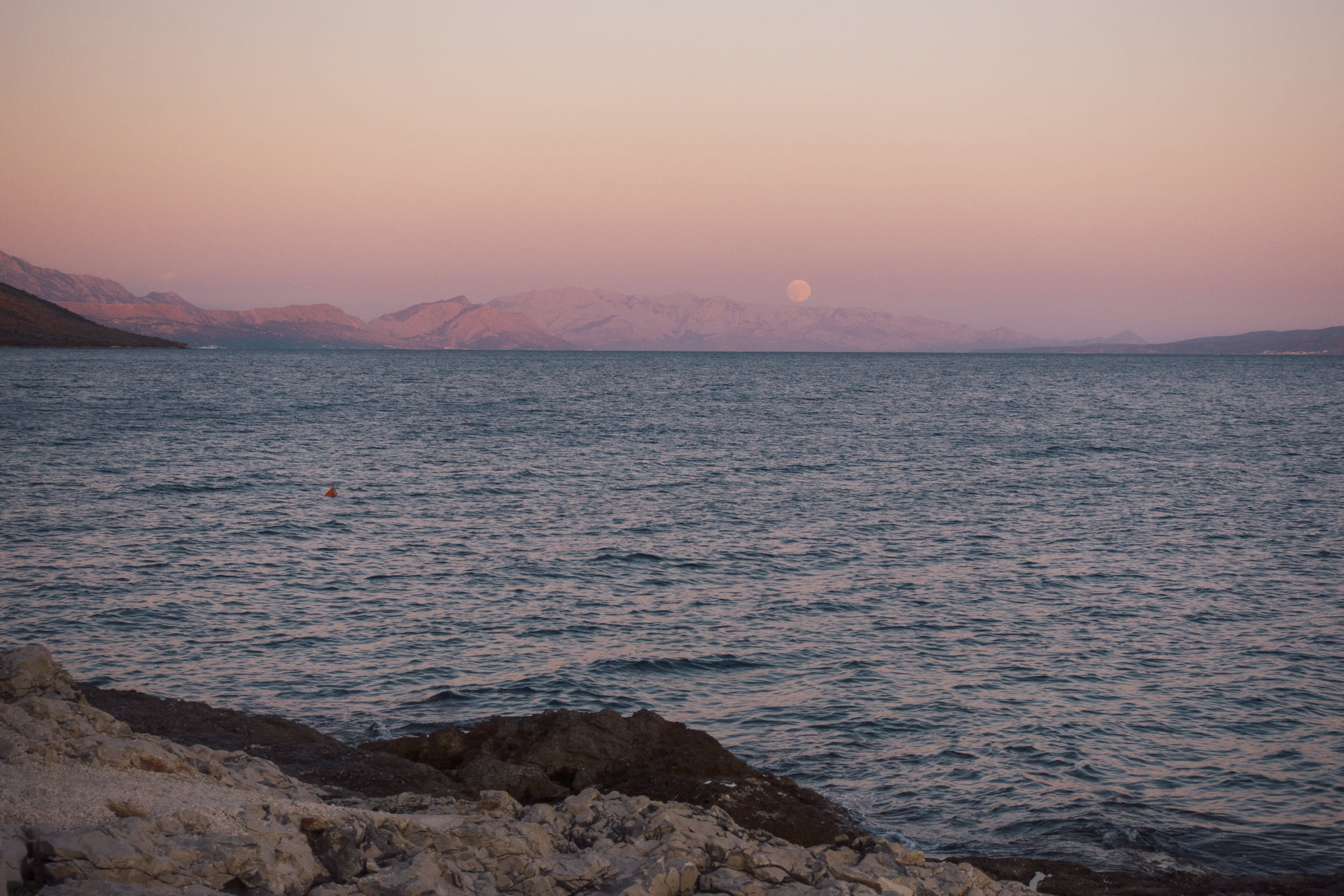 Beautiful seascape with moon rising in the distance.