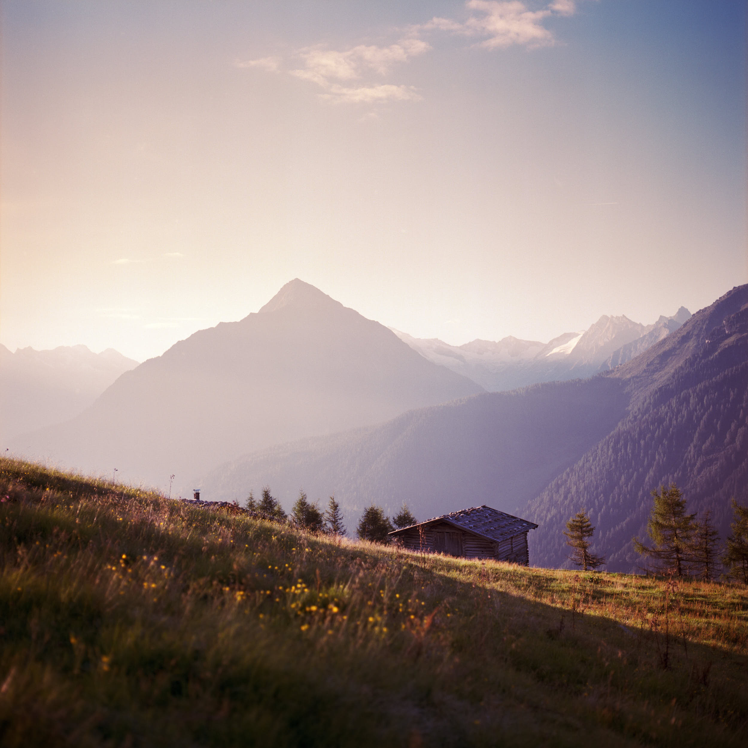 Beautiful landscape photography: morning sunlight hitting alpine peaks with an old wooden shed in foreground.